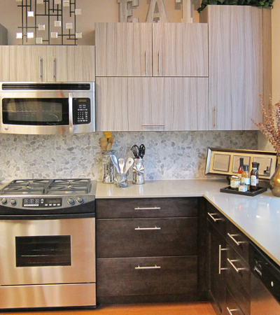 This budget kitchen looks great with budget kitchen appliances. The pebble backsplash tile is inexpensive, but adds just the right amount of texture and pattern. Two toned cabinets with stained cabinets on the bottom in a walnut stained alder and upper cabinets in a laminate looks expensive, but isn't. Simple white quartz cabinets with no reveal looks classy