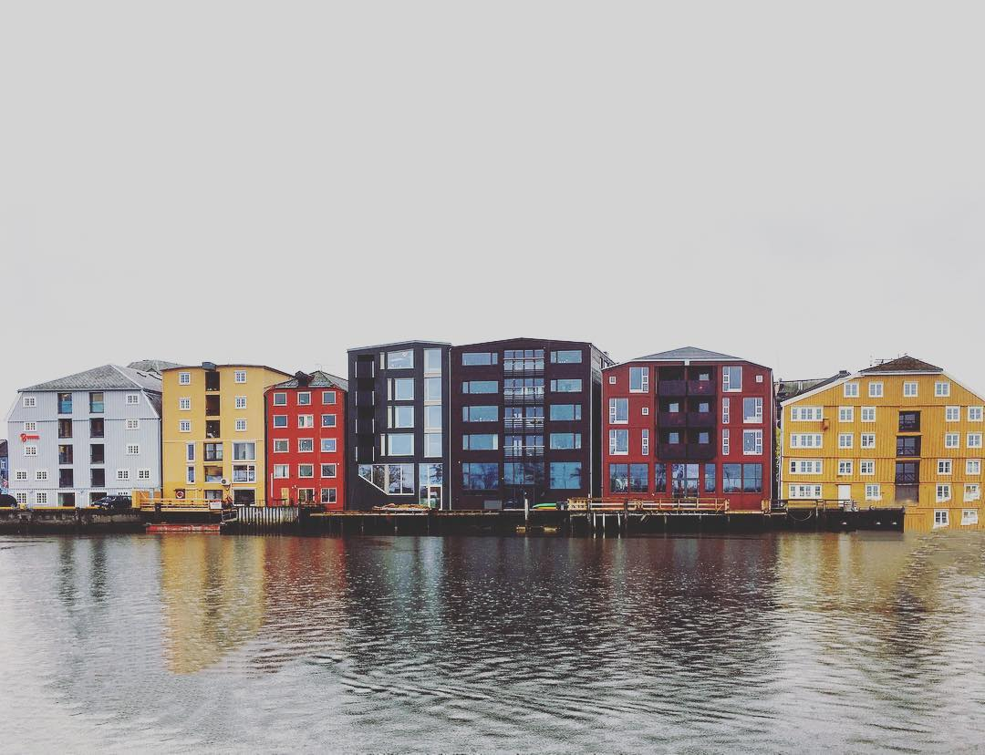 Colorful wooden houses along the channel of the city river Nidelva.