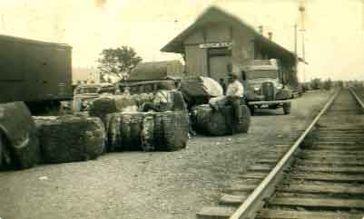 Settlers waiting to load bales of cotton onto the train