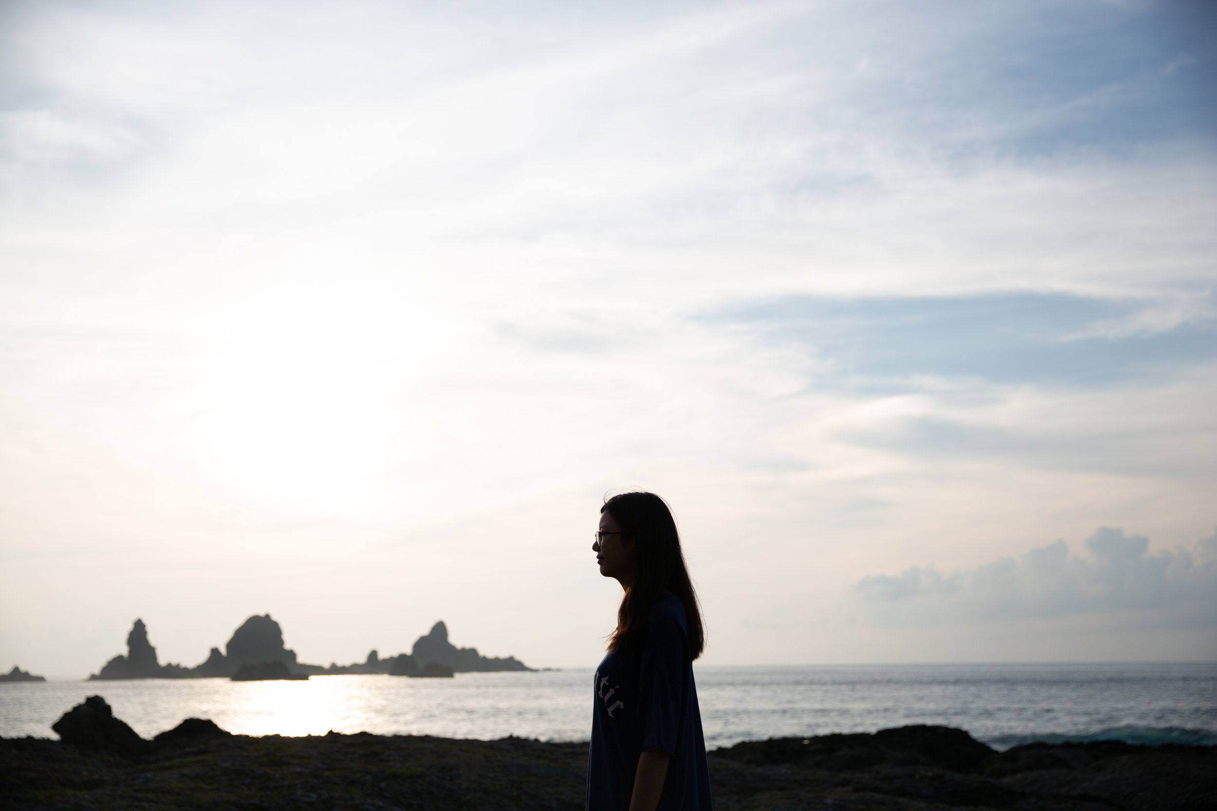 Tranquility  by Yu-Pei Lee:    I took this photo at a small island off of Taiwan, Lanyu. I left the crowded place where everyone was taking pictures of the colorful sunrise and went to a quiet beach. I especially like the reef behind the figure.