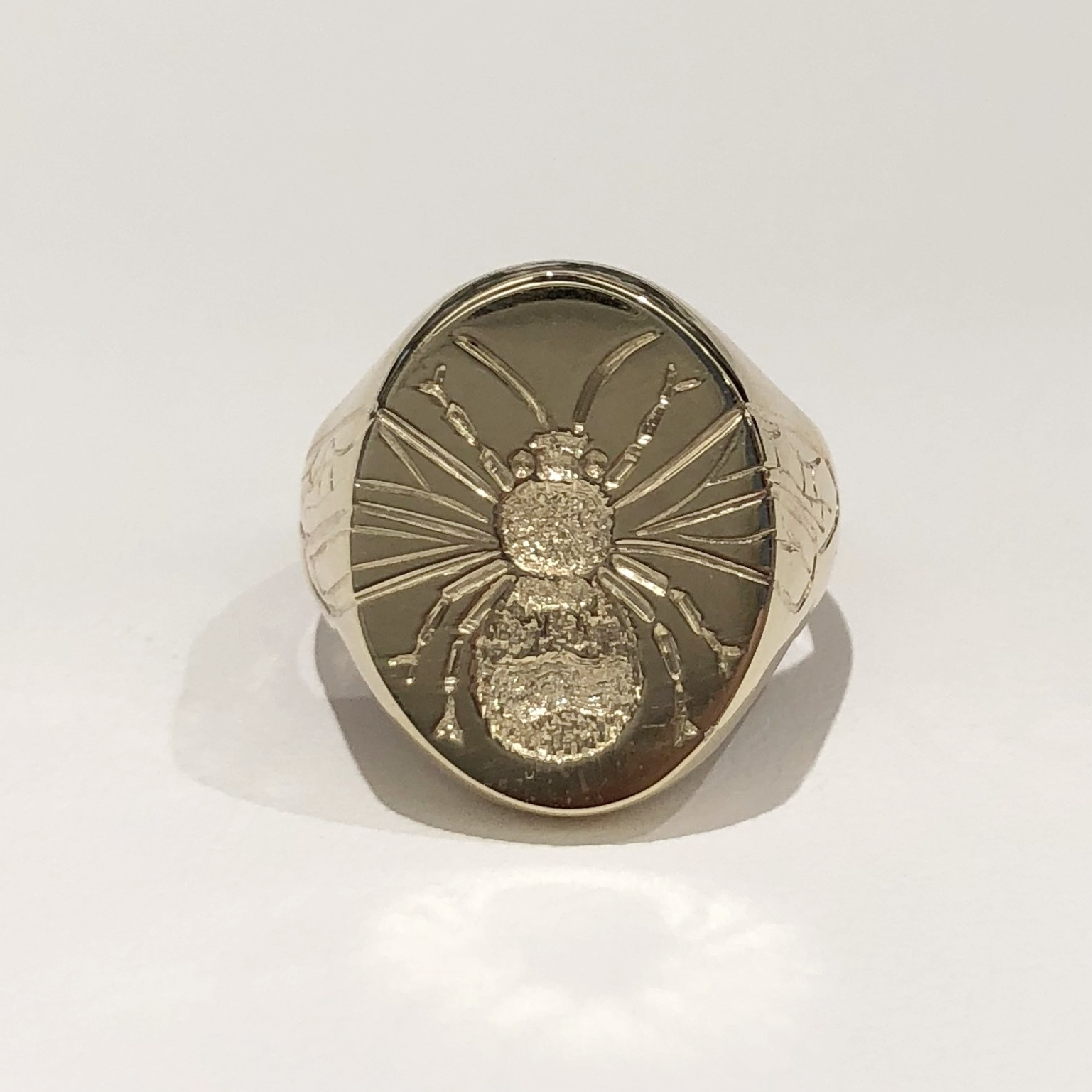 Finished ring with new engraving of a bee.