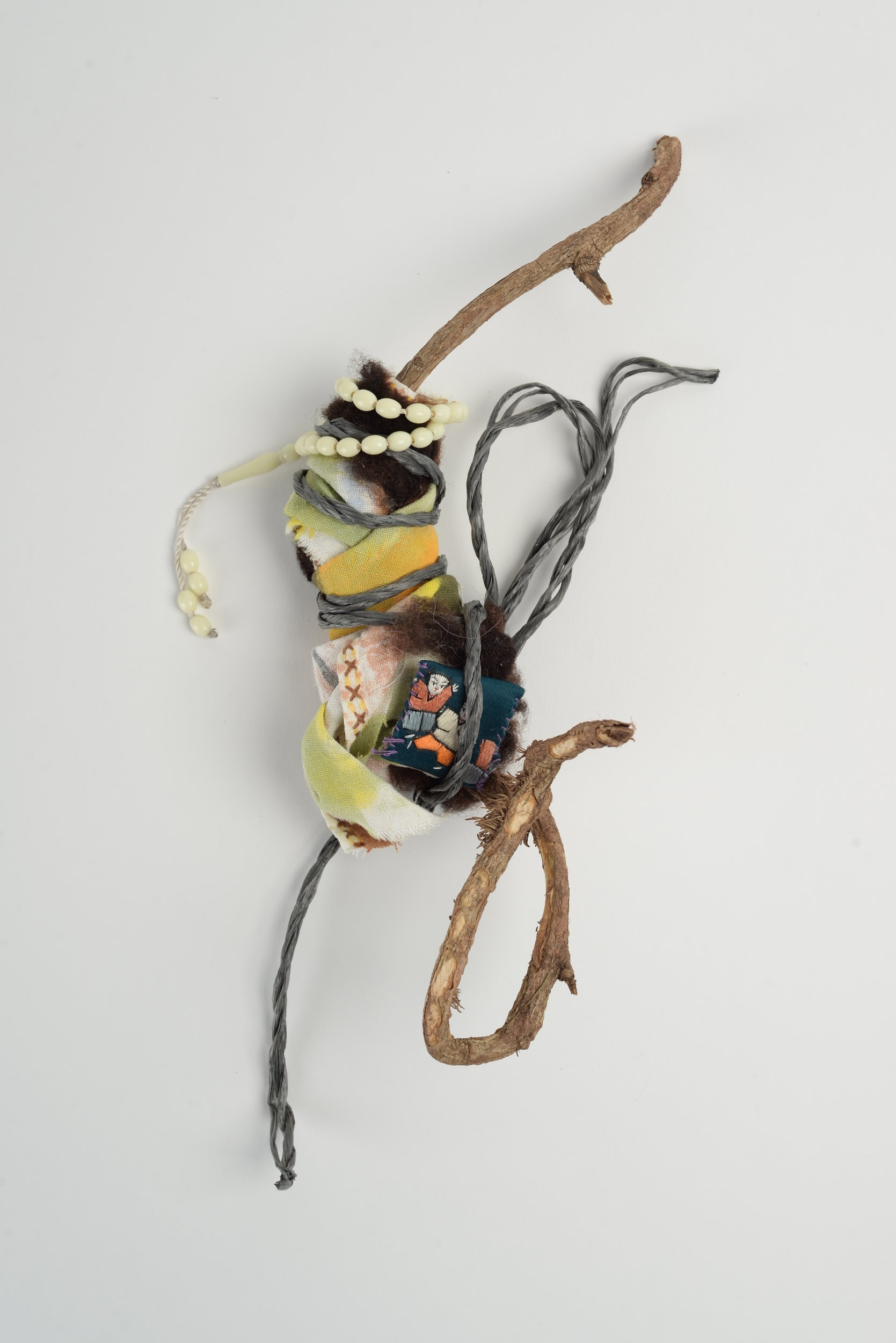 Untitled (prayer),  2018 dried tree root, painted cloth, string, prayer beads, token of gratitude h25cm