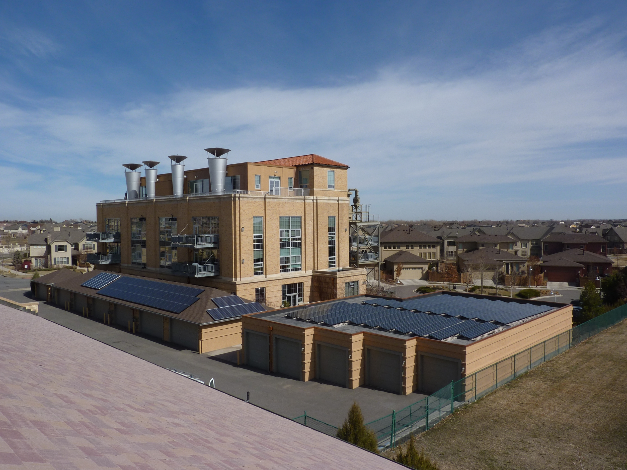 Southwest view showing solar panels on garage roofs