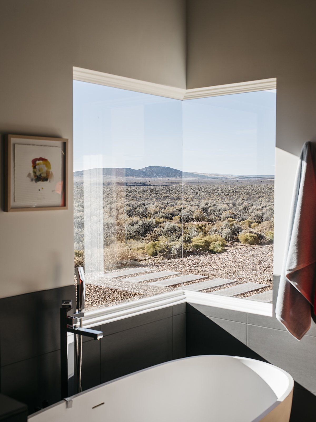 the-master-bathroom-features-one-of-two-corner-windows-in-the-house-at-night-when-i-take-a-bath-i-can-see-the-moon-and-the-stars-says-lois-taos-new-mexico-dwell-magazine-july-august-2017.jpg
