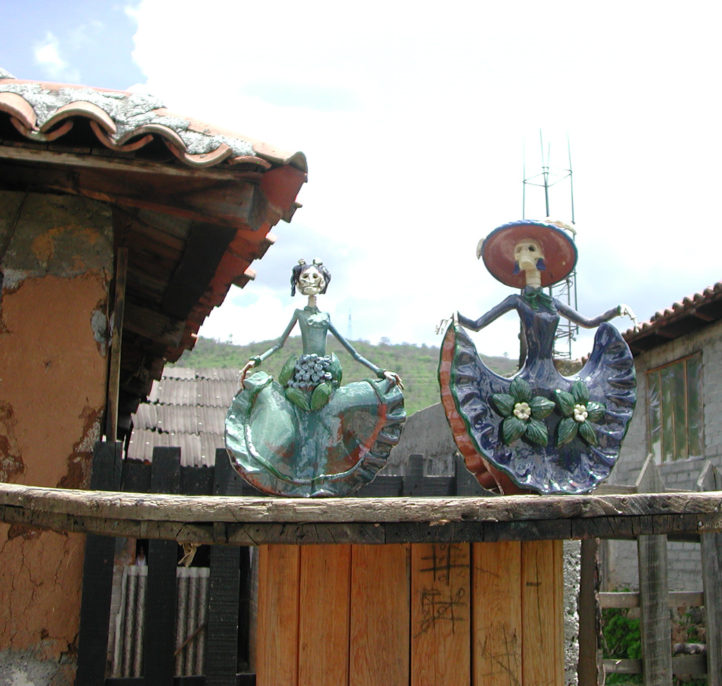 Clay catrinas dance on the fence of a folk artist in Michoacan!