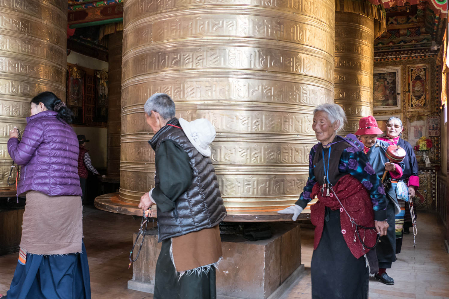 A room with four giant prayer wheels and many devout Buddhists