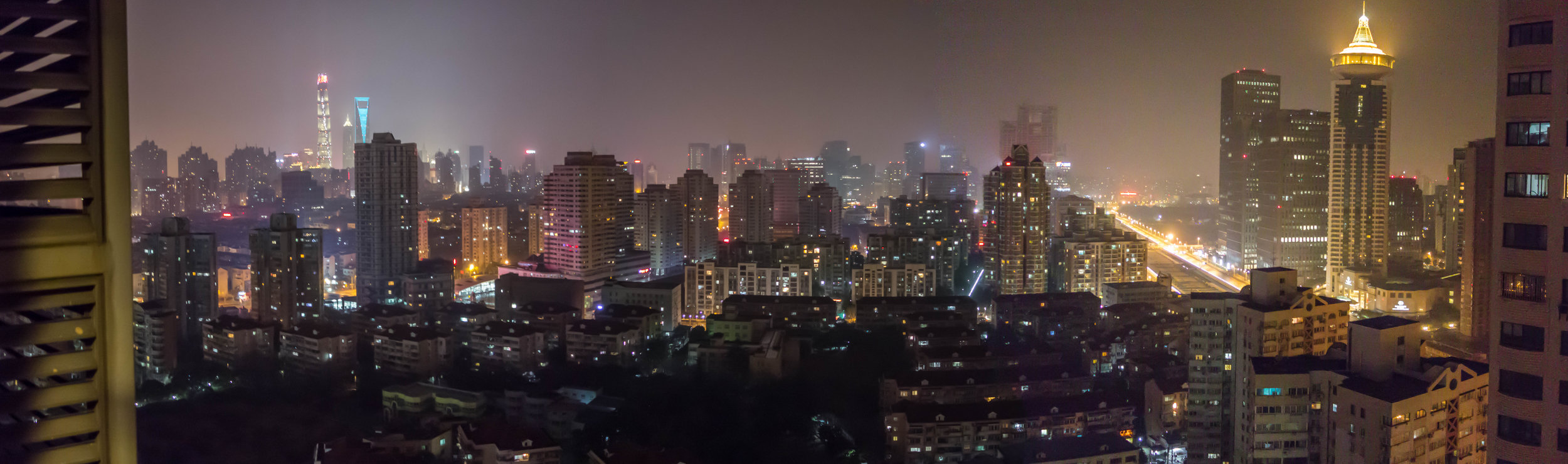 Night view of Pudong from our temporary apartment. Two of the tall skyscrapers are visible to the left in the distance.