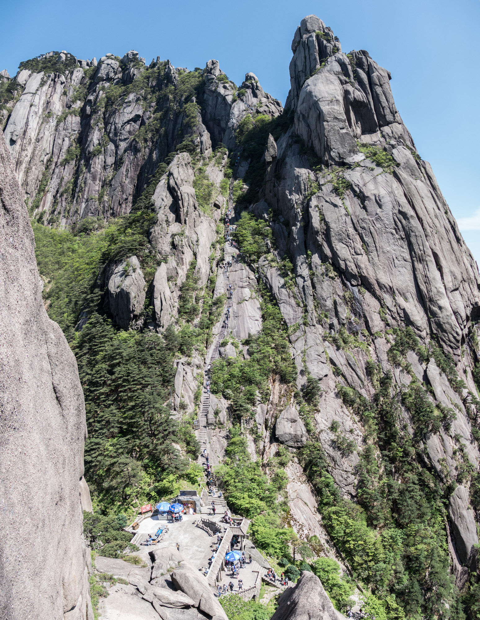 Vertical panorama of Heavenly Capital Peak, an impressive upward climb. See the line of hikers snaking up to the peak.