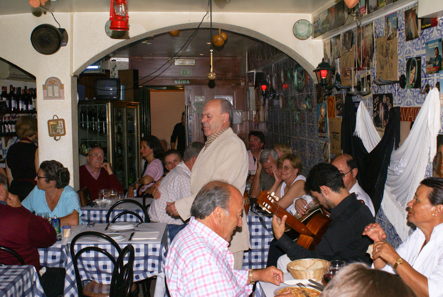 Fado singing in the Alfama.The muscians are on the right and different singers took part. Everyone else in the room semed to know the song and would sing along