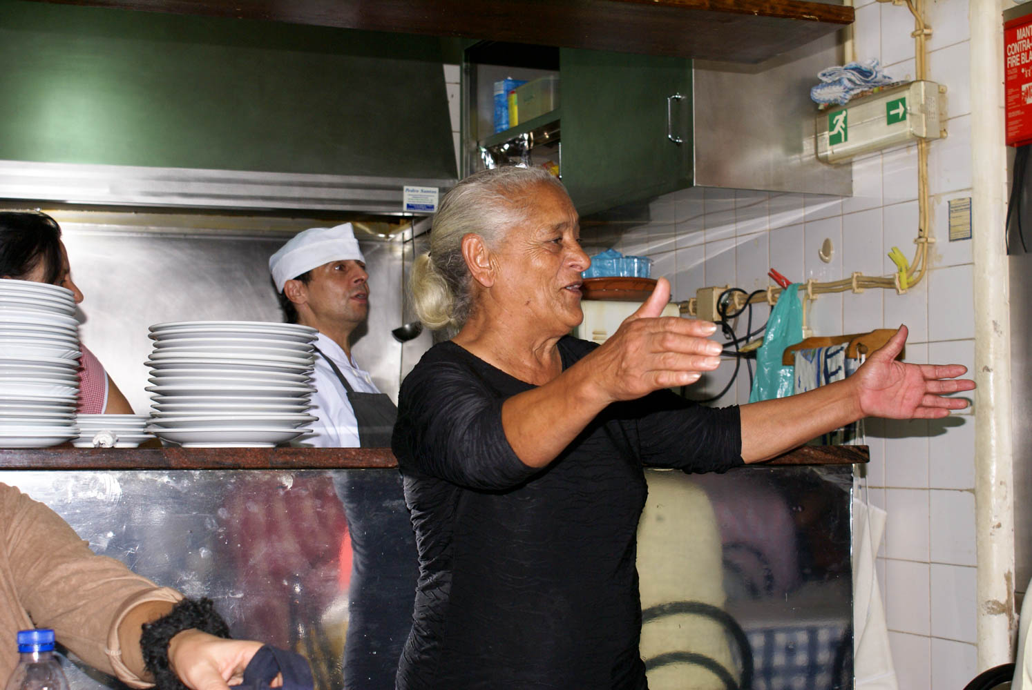 The owner of the small restaurant singing along to the fado singer