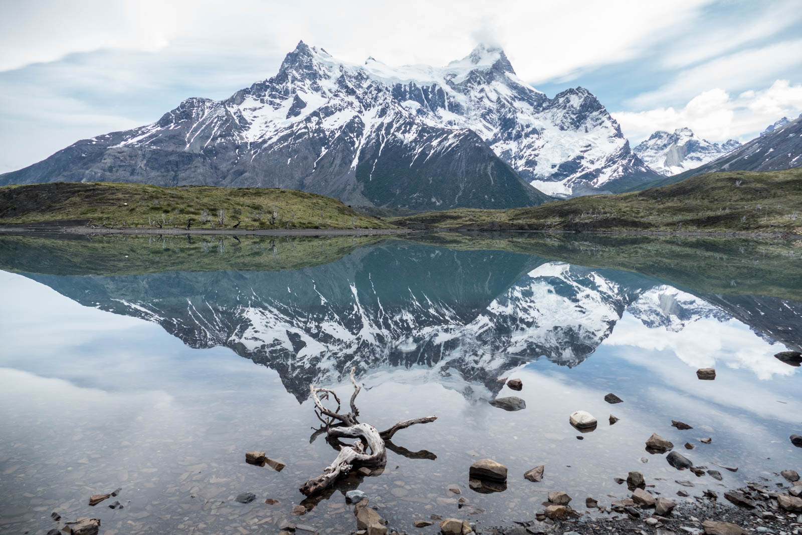 A beautiful laguna with reflection of the mountains on the hike to Mirador Cuernos at an unusual windless moment