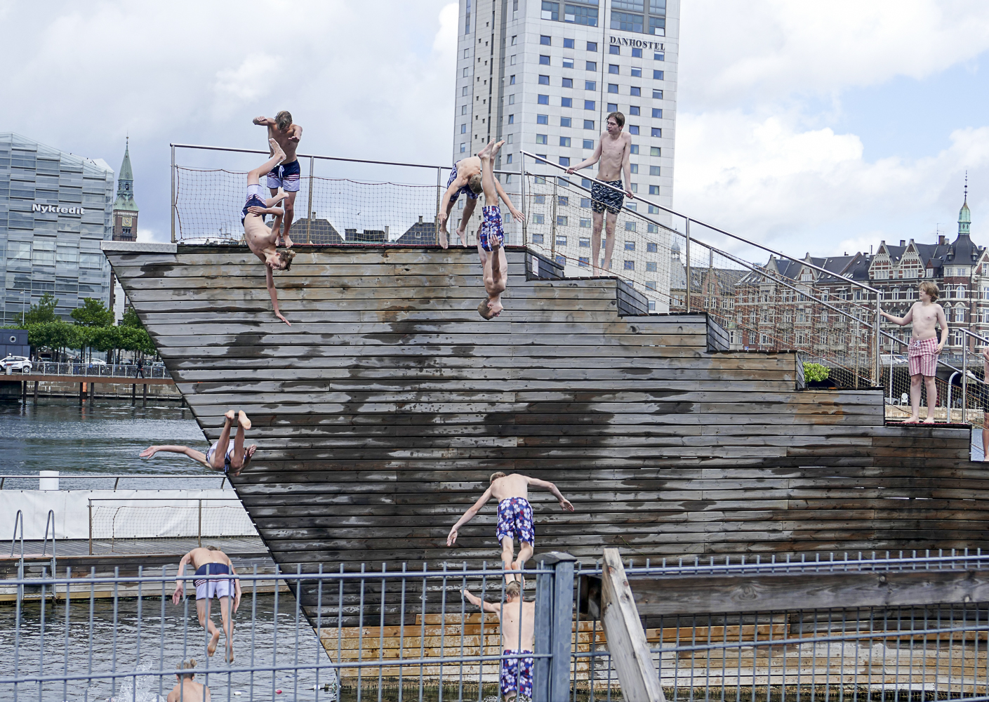 Sequence photo of two kids diving simultaneously into the Havnebadet, a swimming pool which is part of the main waterway, the Copenhagen Havn