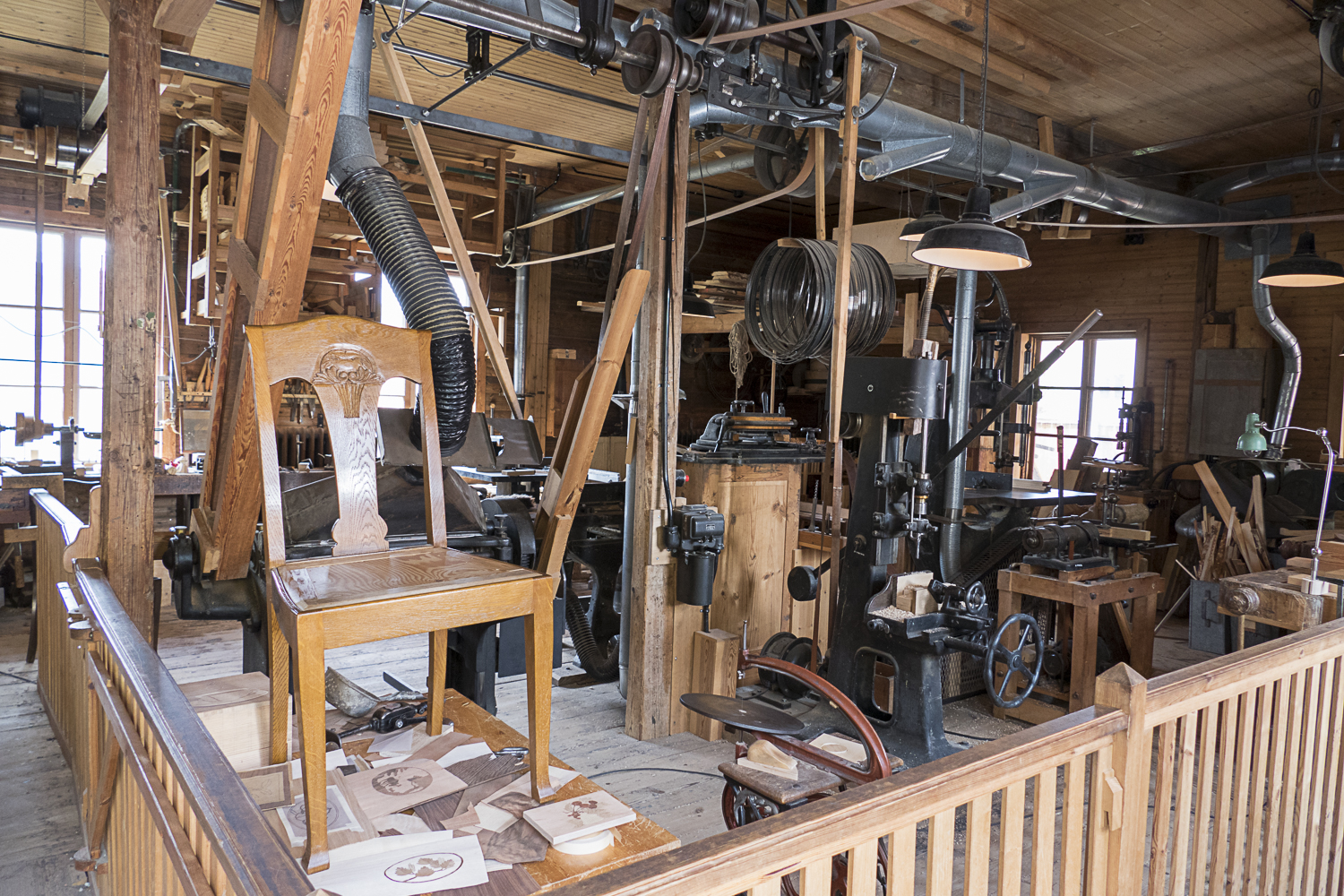 Woodworker's shop with all of the machinery running off a system of belts at the ceiling.