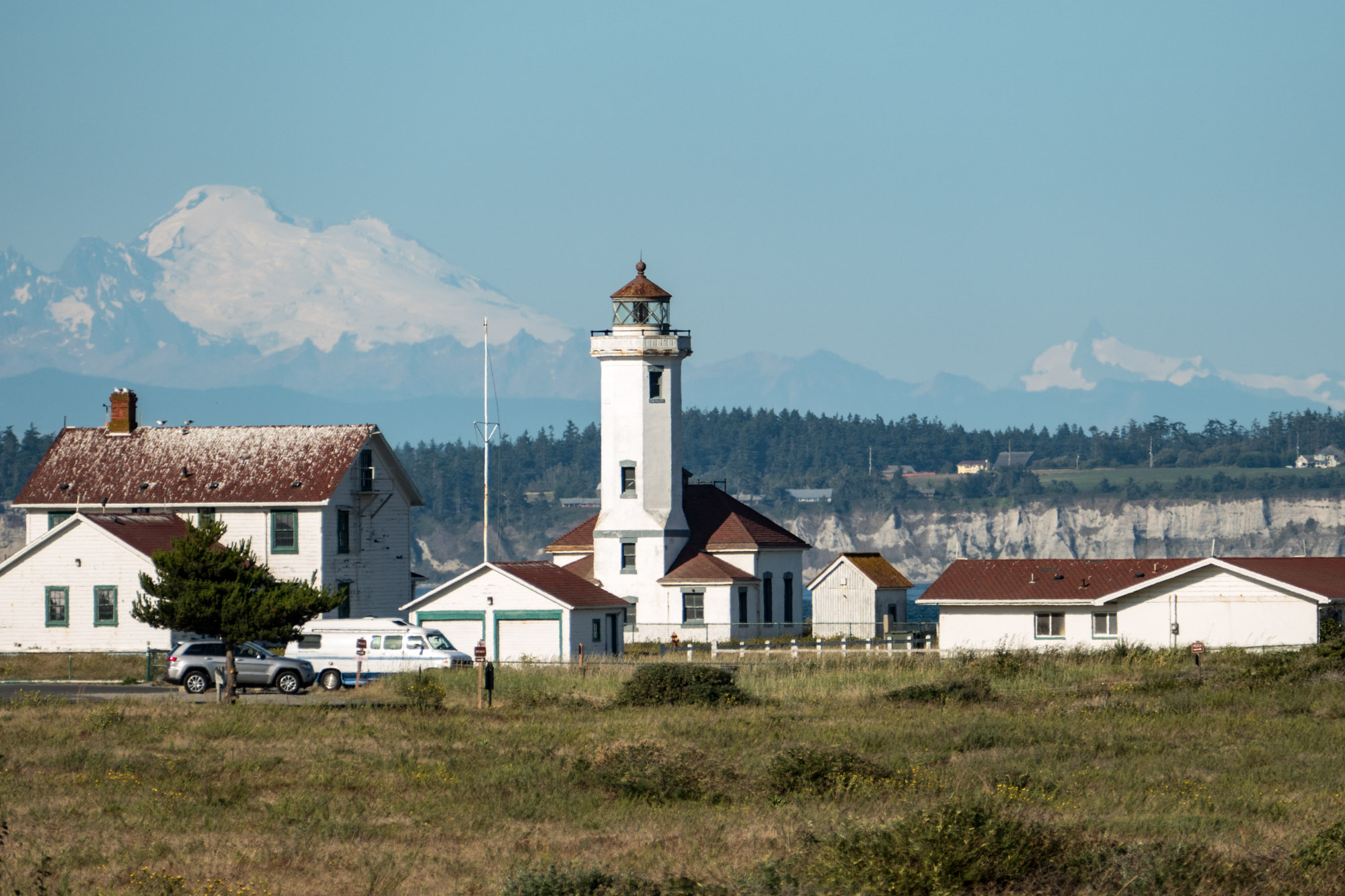 Point Wilson lighthouse with Mt. Baker in the background. With a telephoto lens one can make the background objects appear much larger.