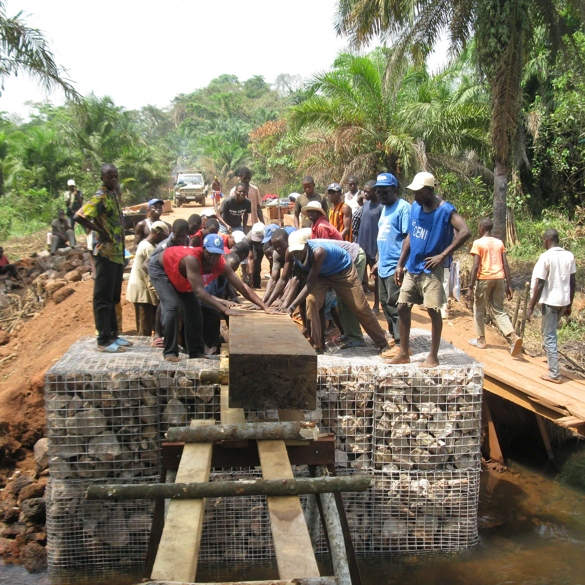 Local laborers building the first bridge in this project, called Llumba bridge. The bridges are designed to be built by hand using mostly local materials.