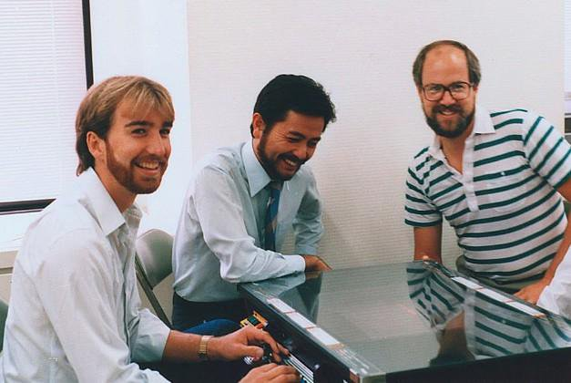 Doug, Scott Tsumura (Irem at the time of photo, now Tozai Games) & Gary Carlston (Brøderbund) with the tabletop arcade version of Lode Runner. Japan 1984.