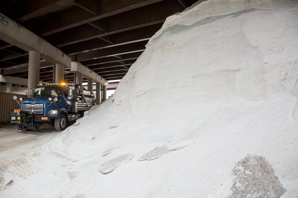 Photo Credit:  Evan Frost  |  MPR News   A snow plow drives past a salt pile underneath an overpass after being filled up in Minneapolis on Mon. Dec. 11, 2017. Evan Frost | MPR News