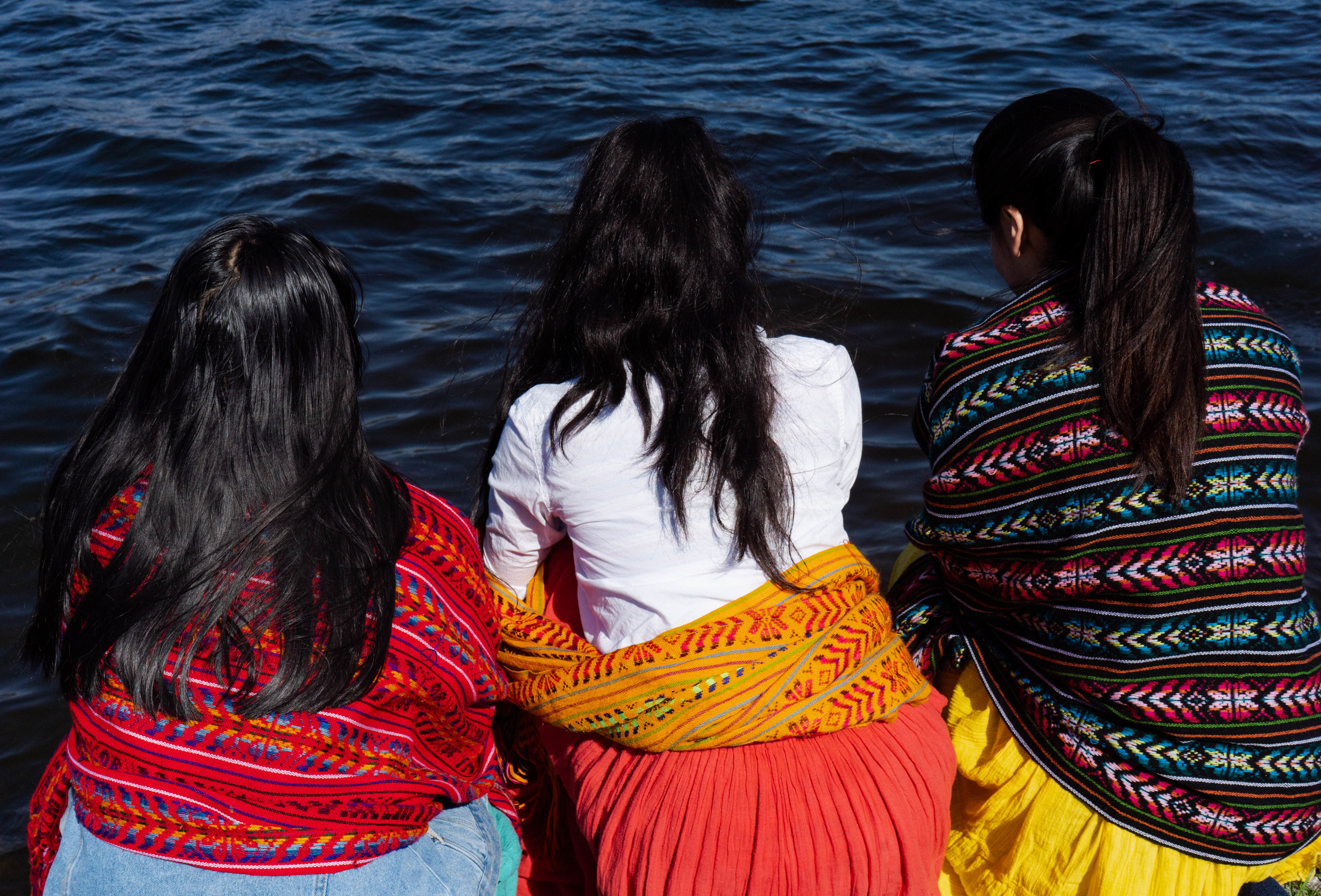 Reyna Day (left), Atquetzali Quiroz (middle), and Amoreina Espinosa (right) staring out to Lake Phalen before the water ritual.