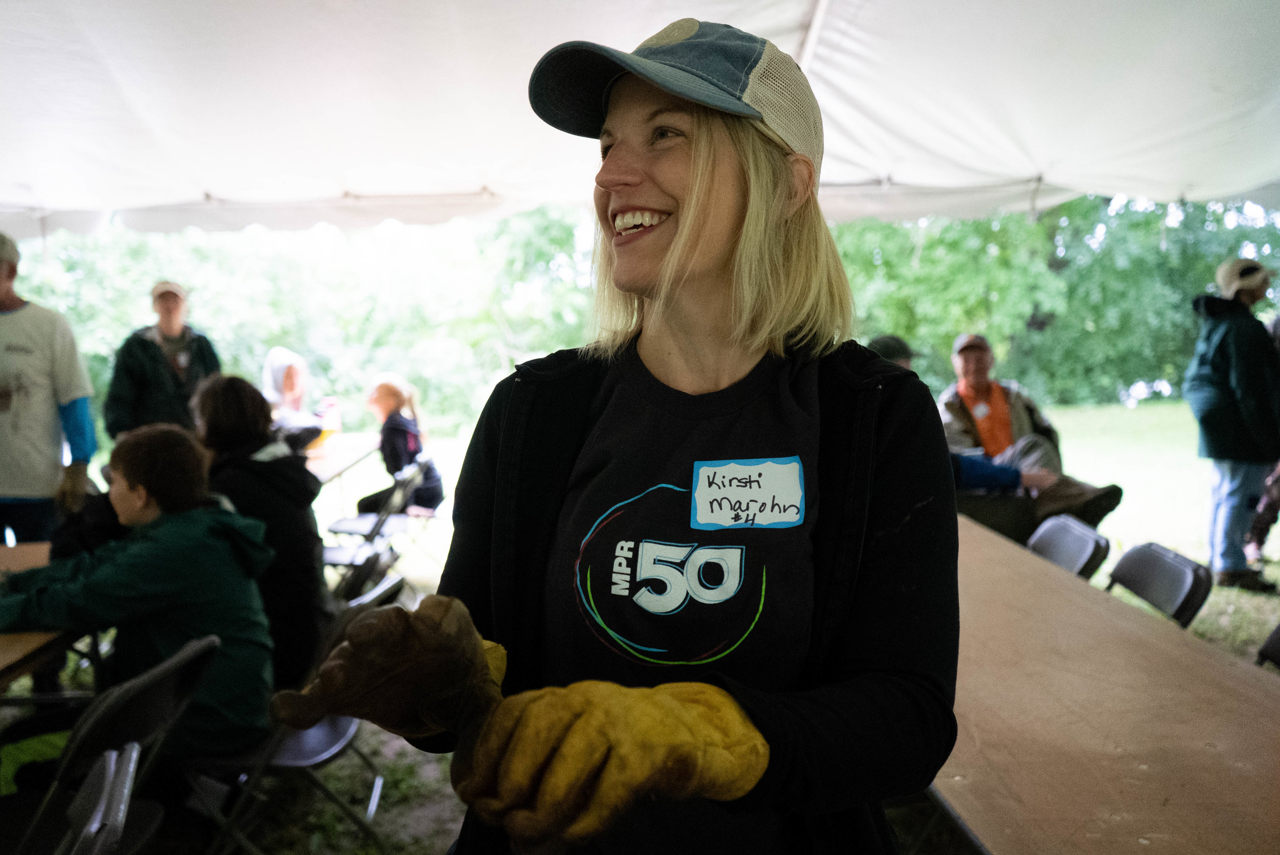MPR News environmental reporter Kirsti Marohn pulls on a pair of work gloves, preparing to help restore the oak forest at Talahi Woods in St. Cloud, on the banks of the Mississippi River.  Iyana Esters   The Water Main