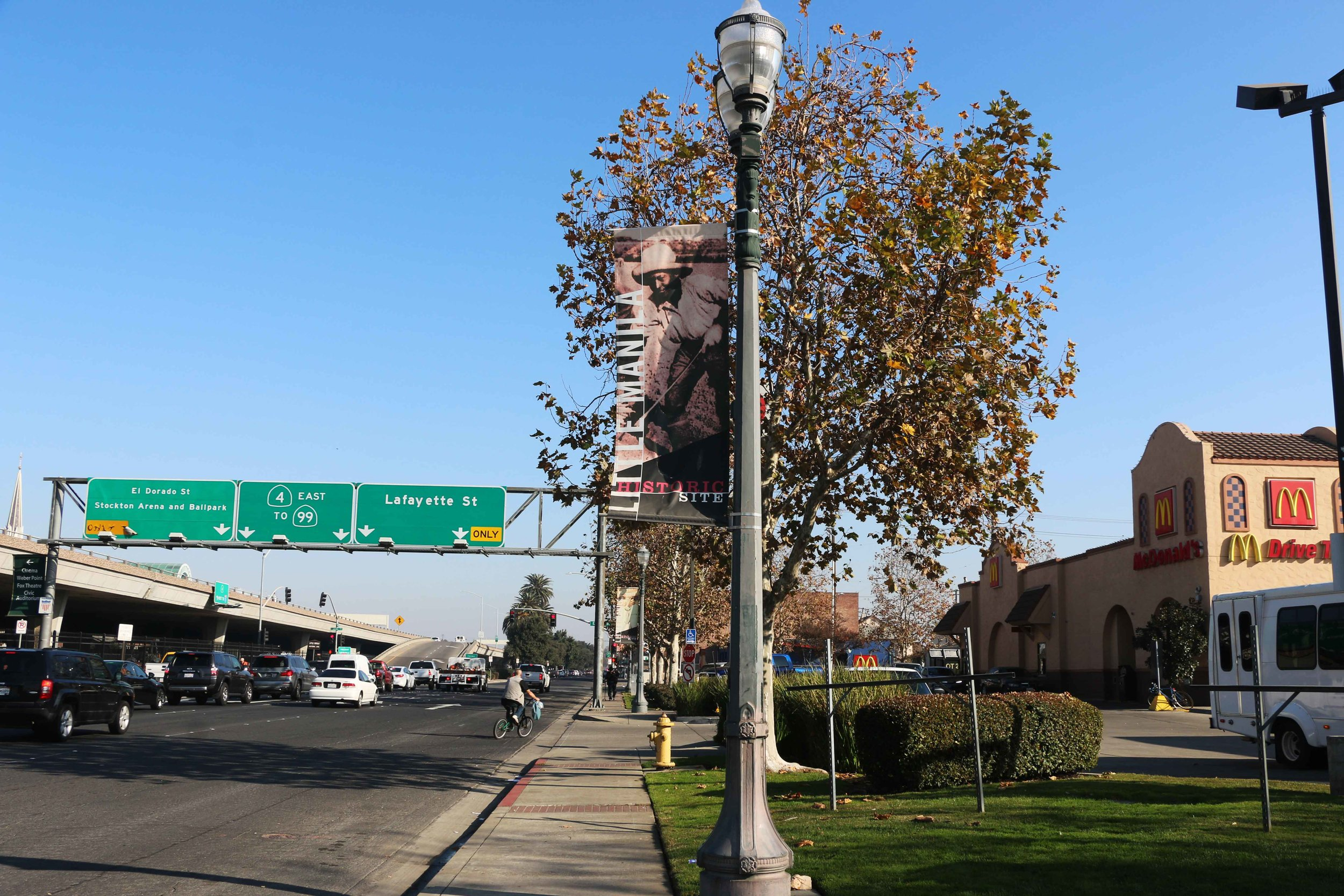 A banner marking the Little Manila Historic Site in Stockton, California is surrounded by a freeway, a gas station, and a McDonald's. Photo by Patrick Epino.