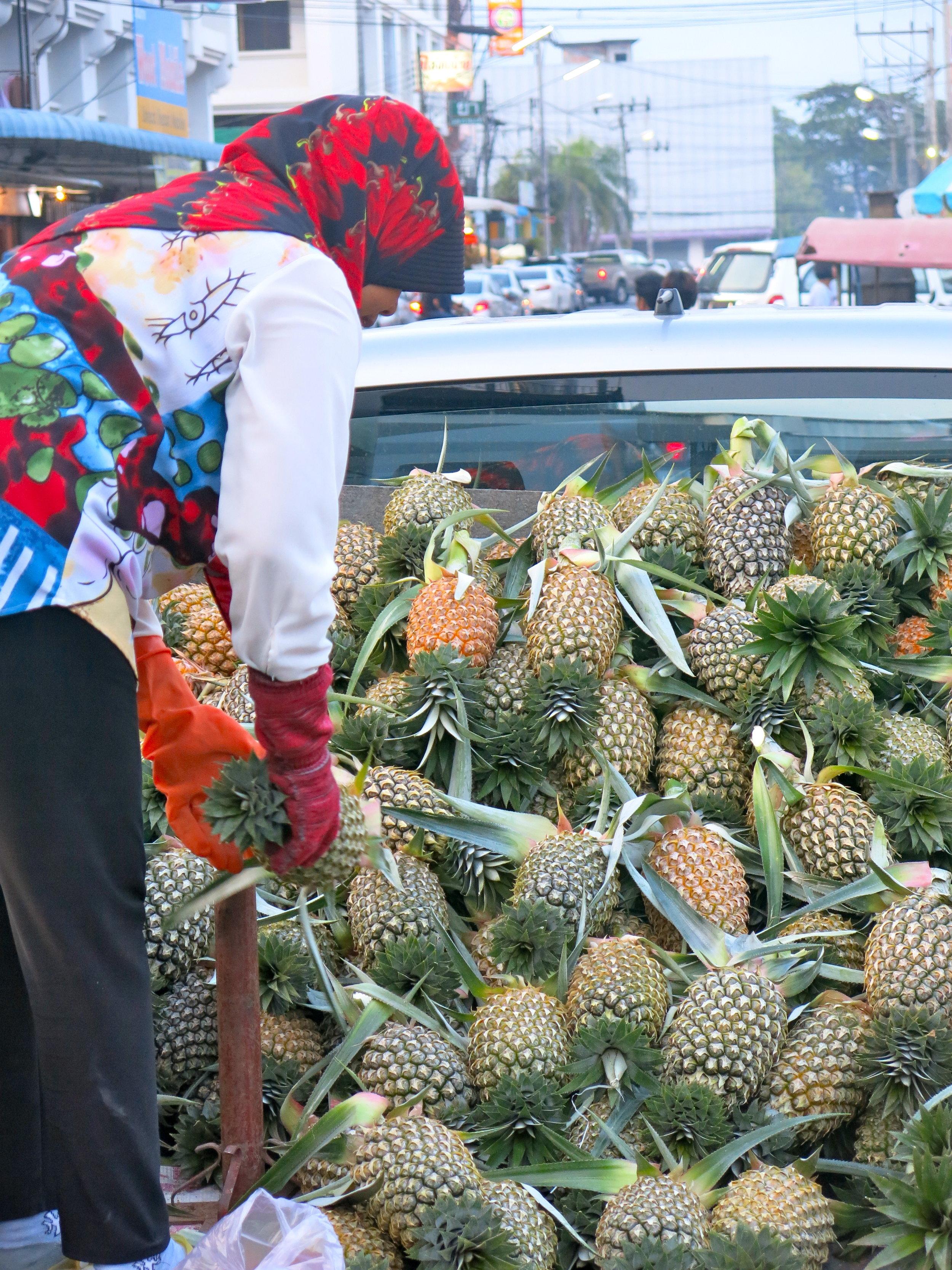 Muslim woman disembarking pineapples at Krabi Town market