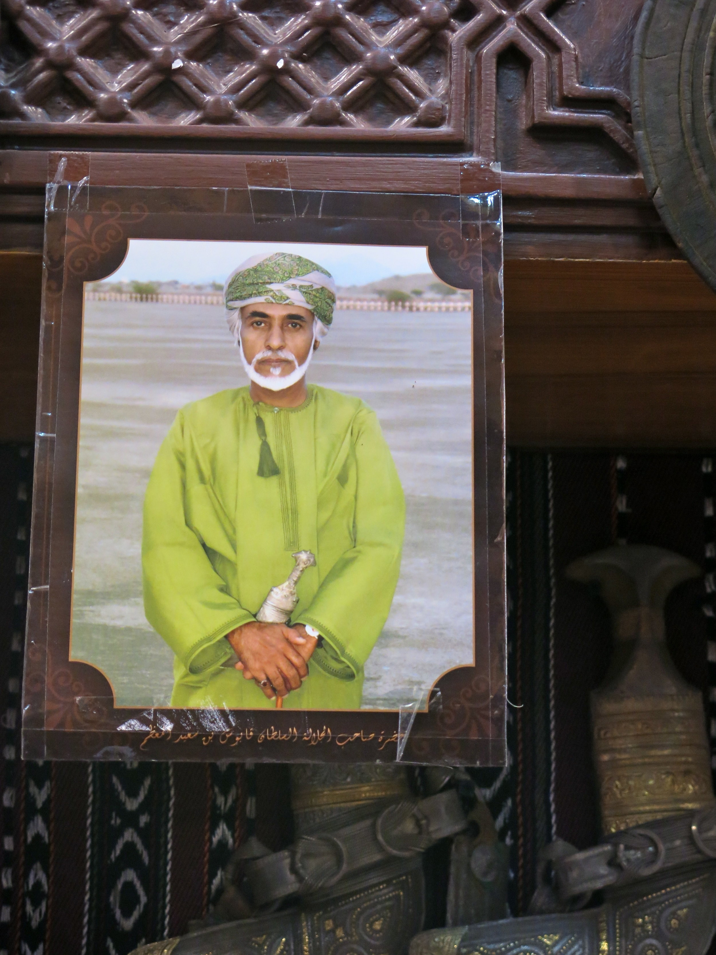 A portrait of Sultan Qaboos hanging in a souk