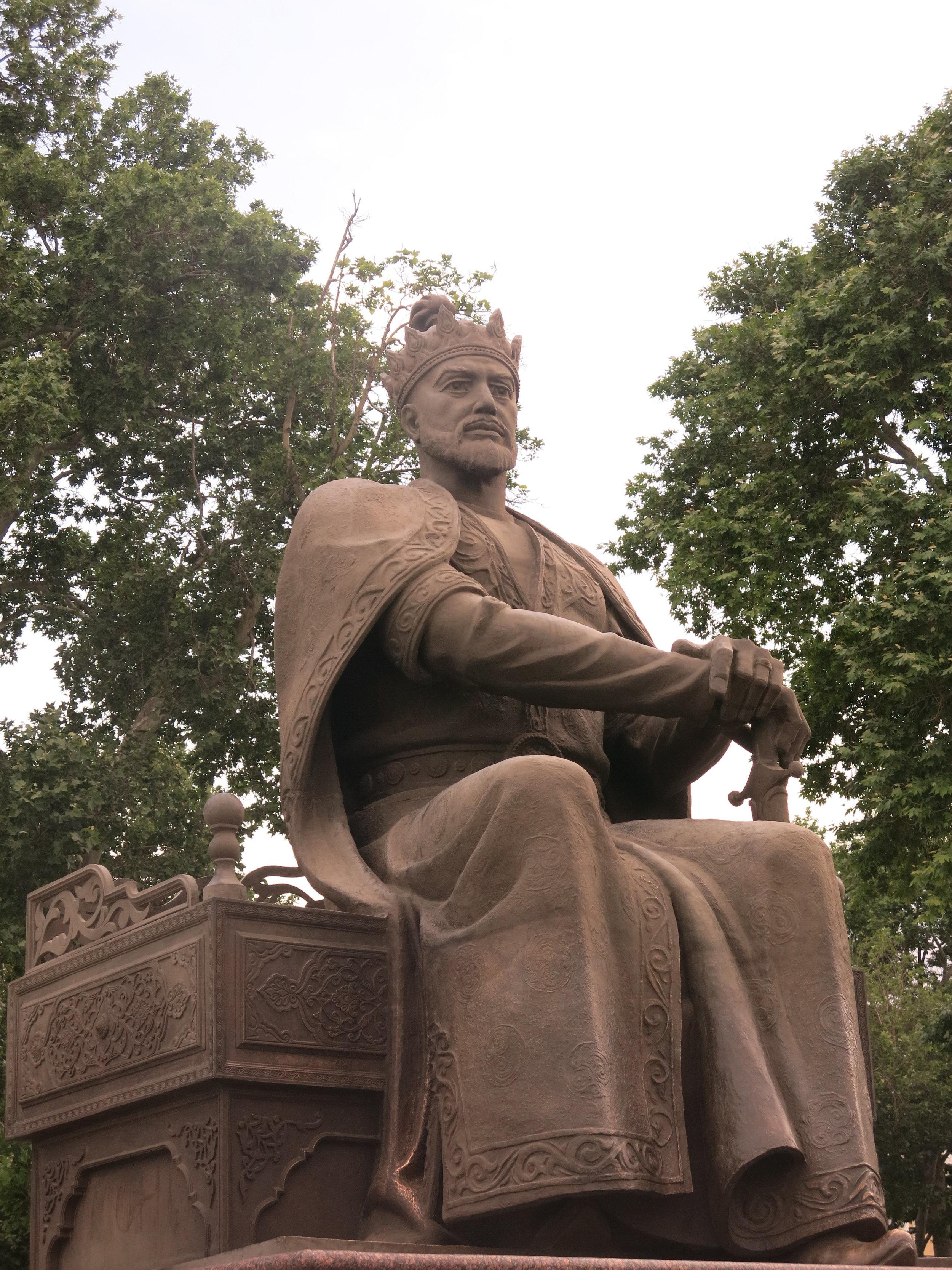 A statue of Amir Temur (Tamerlane) next to a modern boulevard
