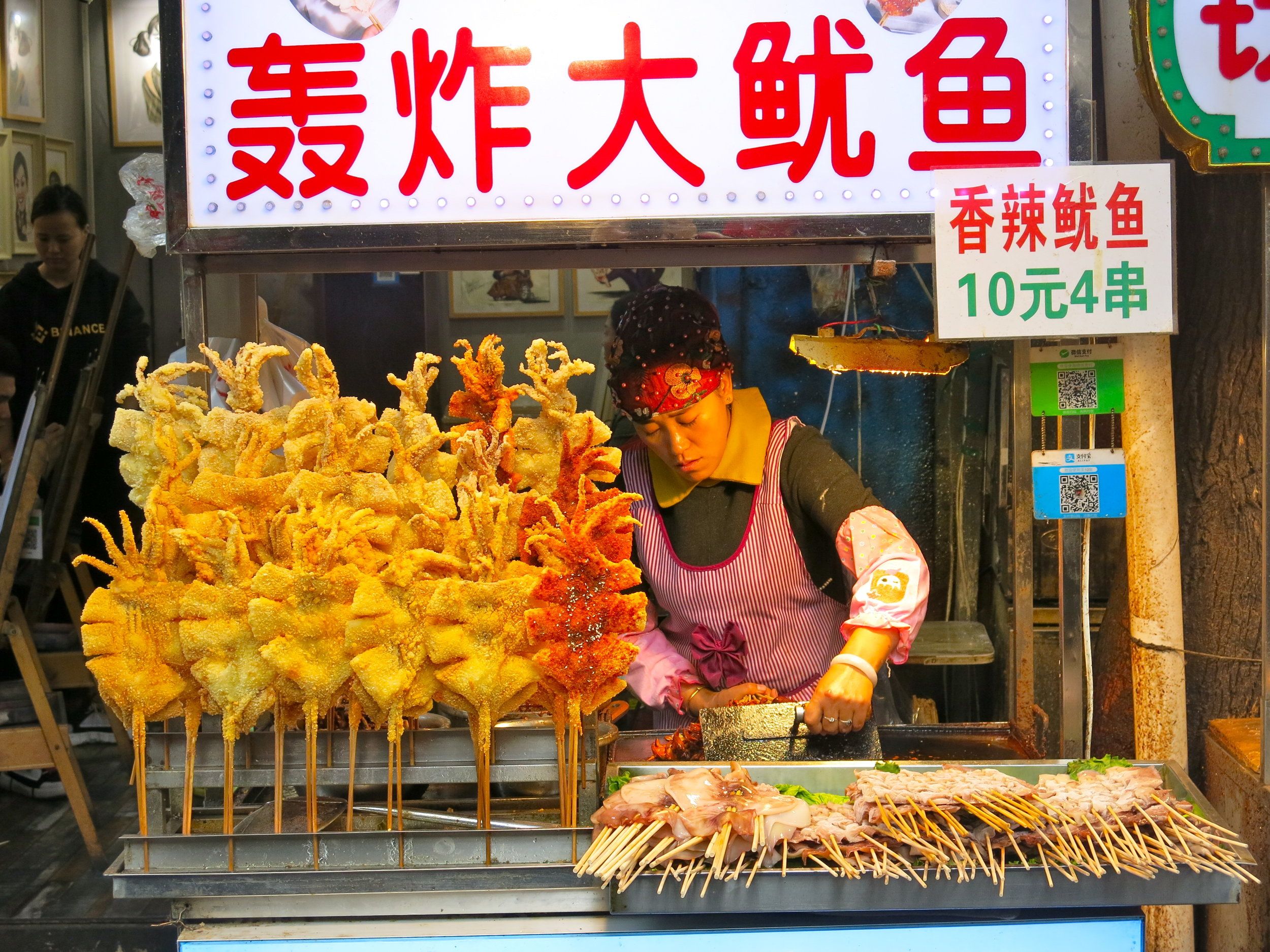 Woman selling squid on a stand