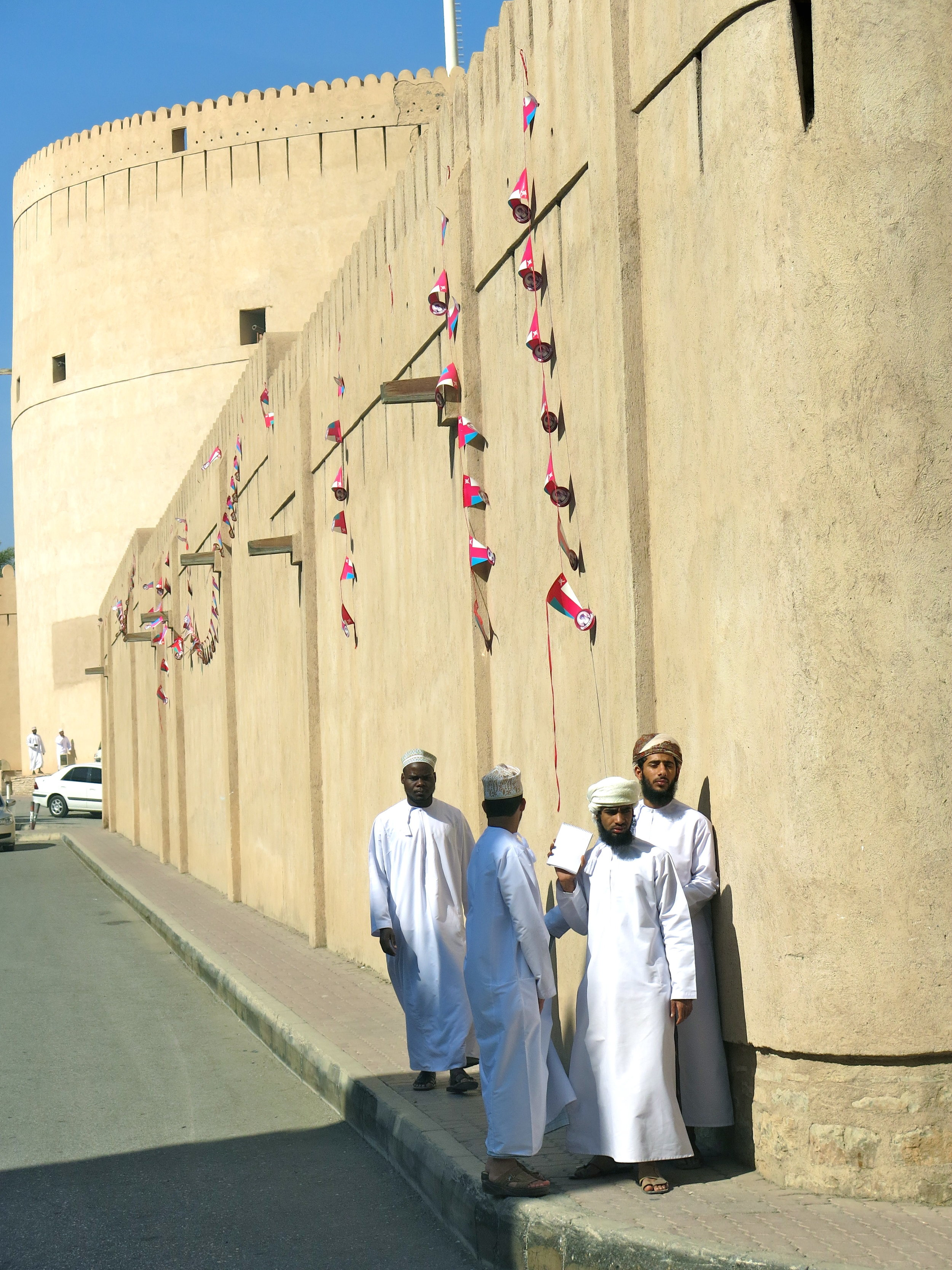 Omani men in traditional white dishdasha next to the old Fort