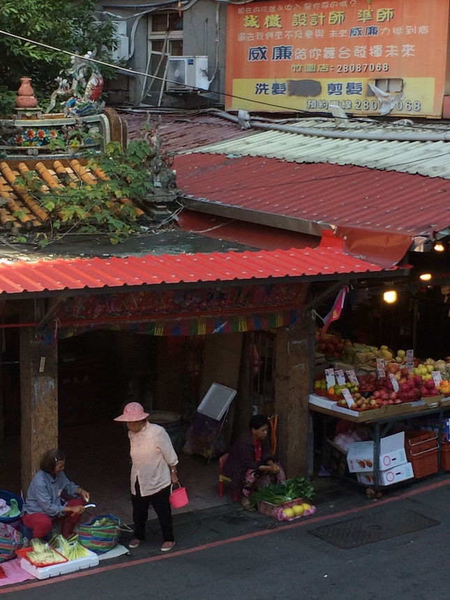 Traditional market-sellers of vegetables, meats, and fruits outside a tiny local temple in nearby Zhuwei