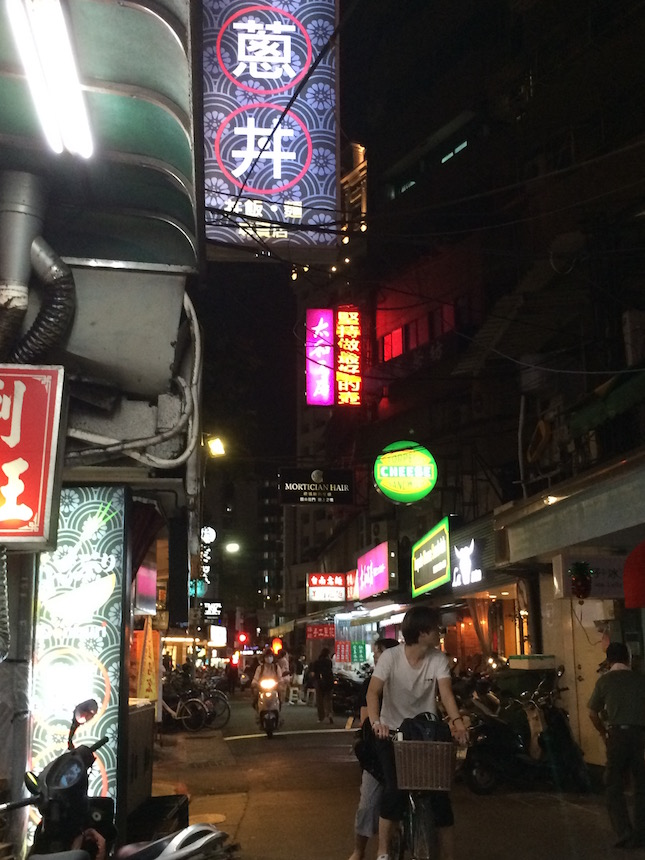 Typical back-street view at night in Taipei, with bicycles, motorbikes, lights, sounds, and smells