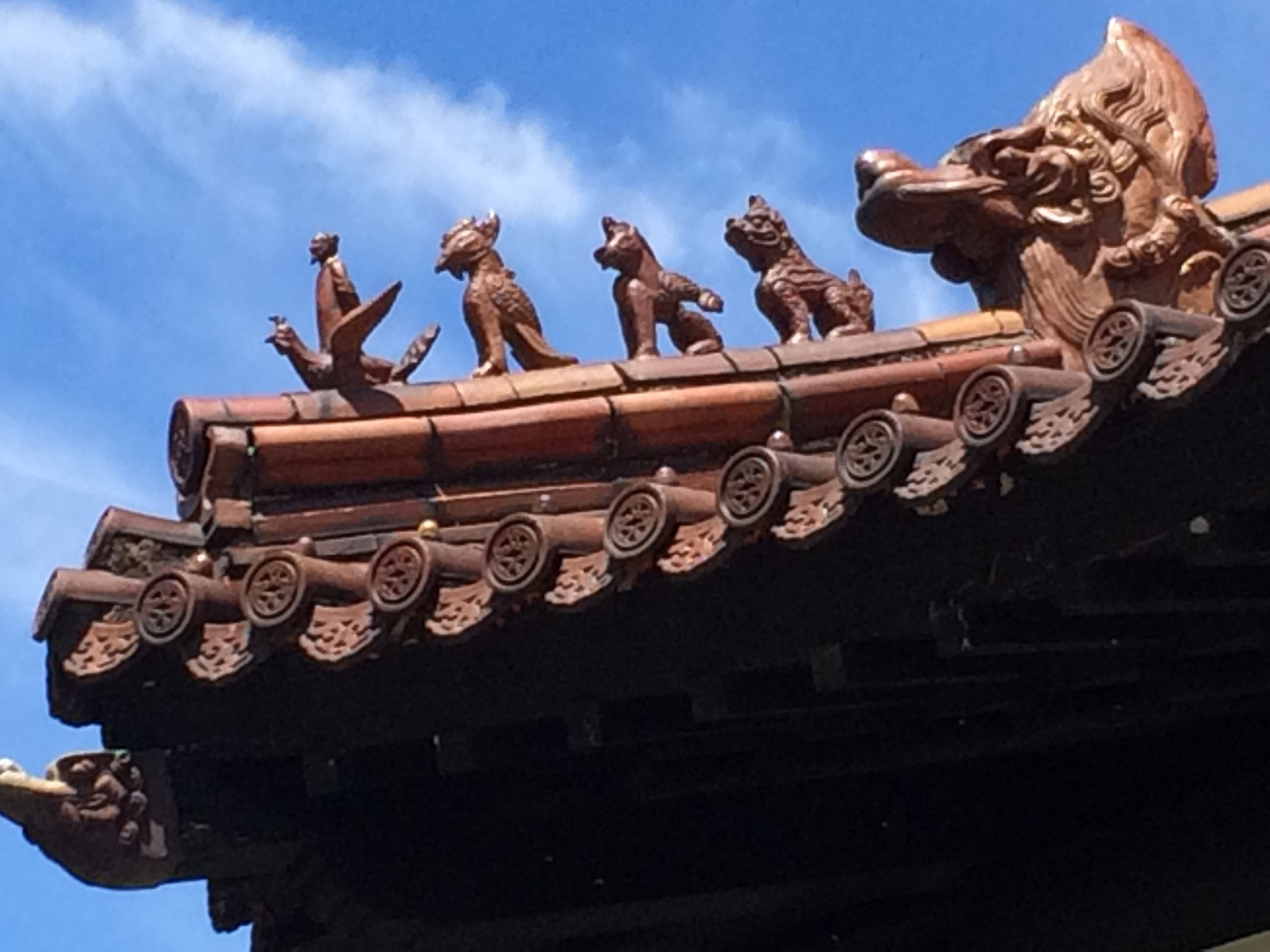 Monk standing on a bird, and other roof ornaments on a pavilion at the Memorial Peace Park