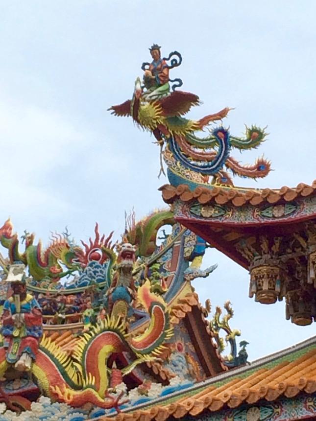Regal woman on a crane on Guandu Temple rooftop