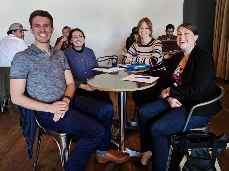 Four members of the MACA board sit around a table during a board meeting in April 2018.