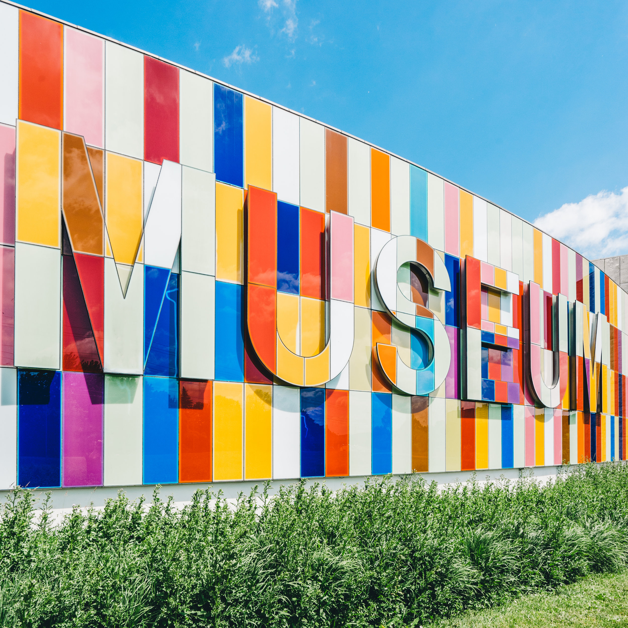 The word Museum is spelled out in colorful tiles alongside a building.