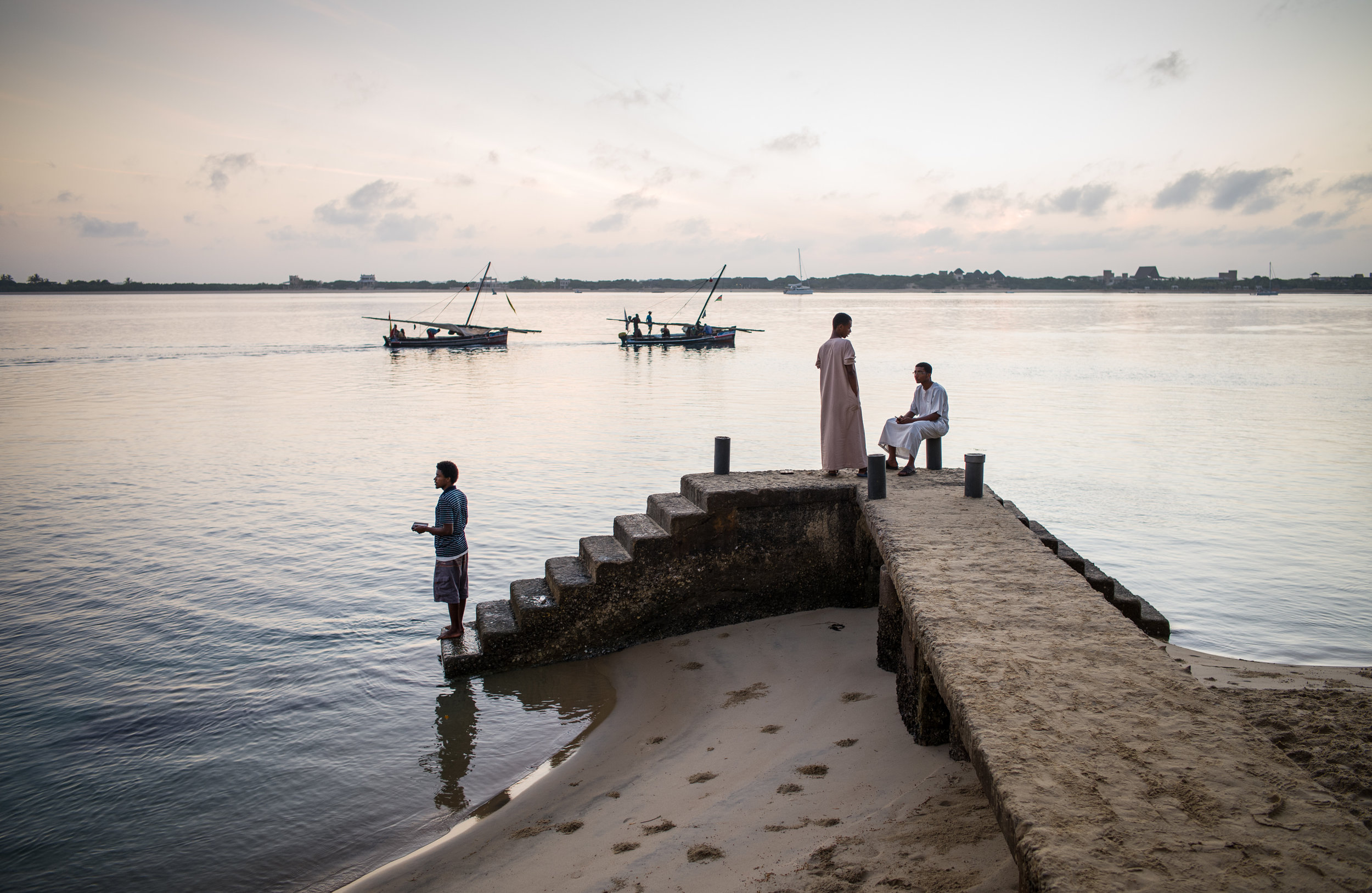 Young men linger on Shella pier on Lamu Island in Kenya as fishermen head out to sea aboard their jahazis – a type of dhow sailing vessel