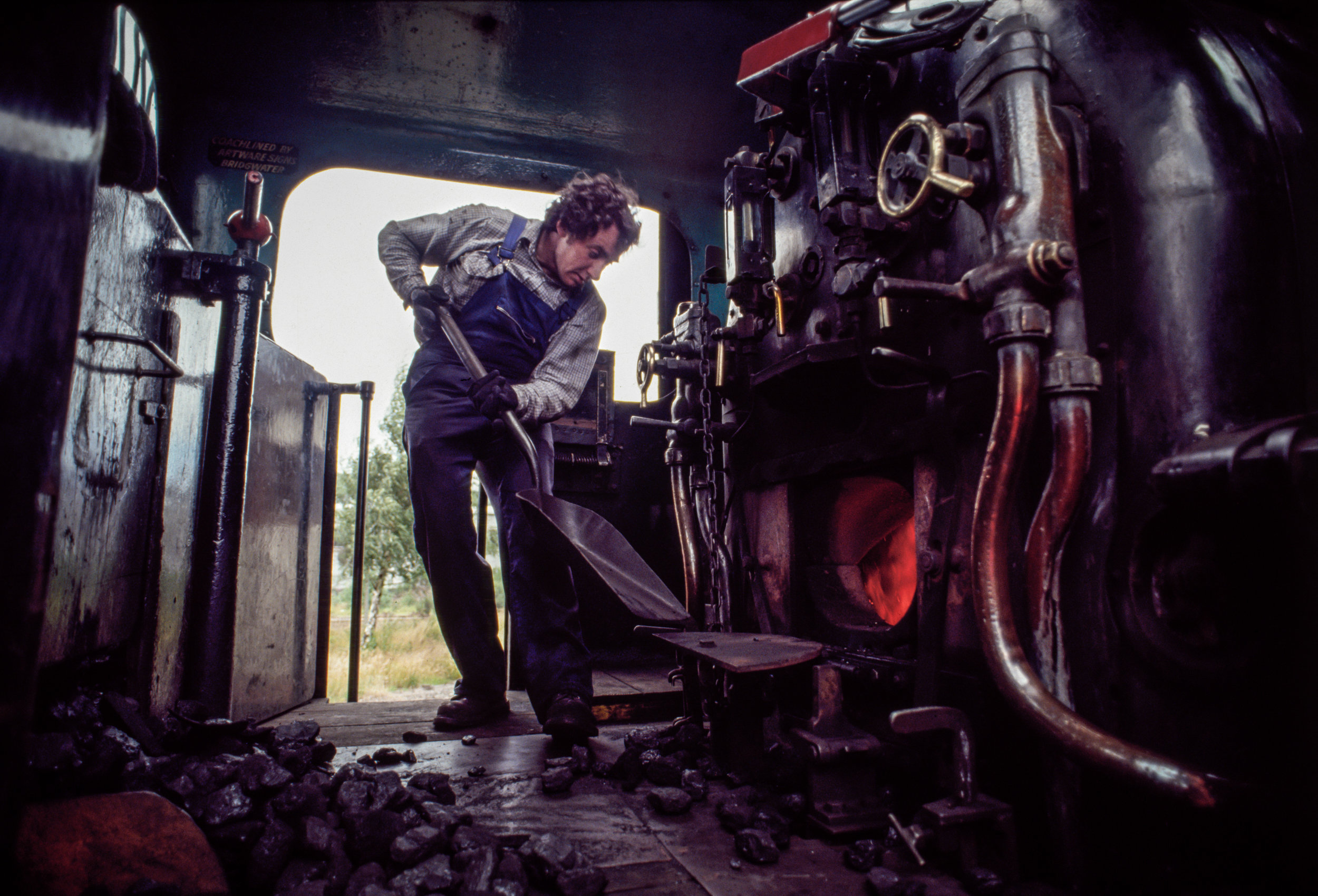 A fireman for the Strathspey Railway shovels coal into the boiler of a locomotive en route from Boat of Garden to Avimore in Scotland