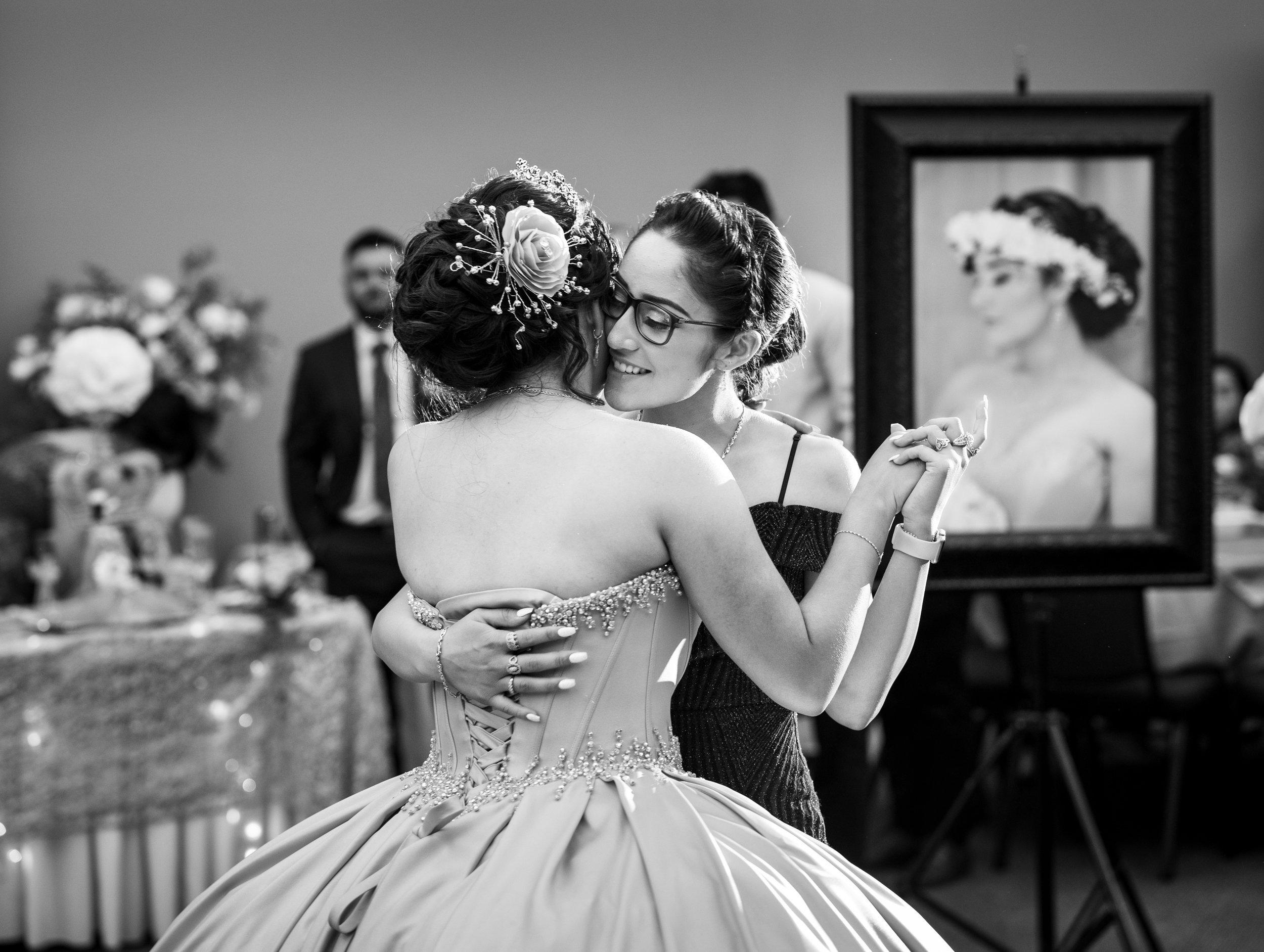 Adriana Gonzalez dances with her sister Paola Gonzalez during Adriana's quinceañera in Sacramento, California