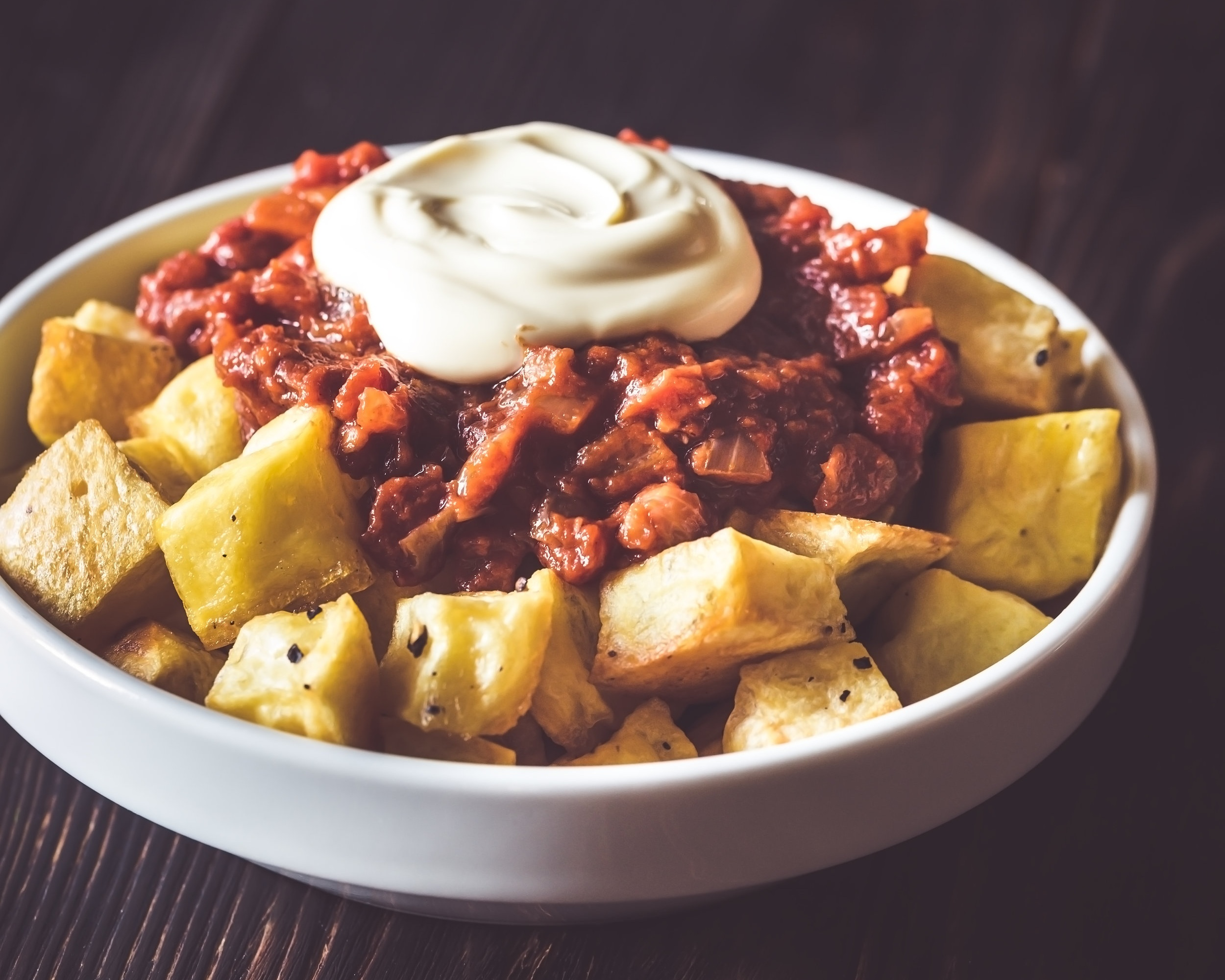 Patatas Bravas - Keep things simple with cube-cut potatoes, fried in oil and served warm with a sauce such as a spicy tomato sauce or melted cheese.