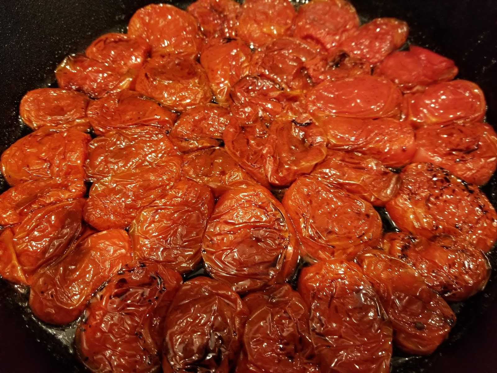 Oven roasted tomatoes arranged in 12 inch cast iron pan