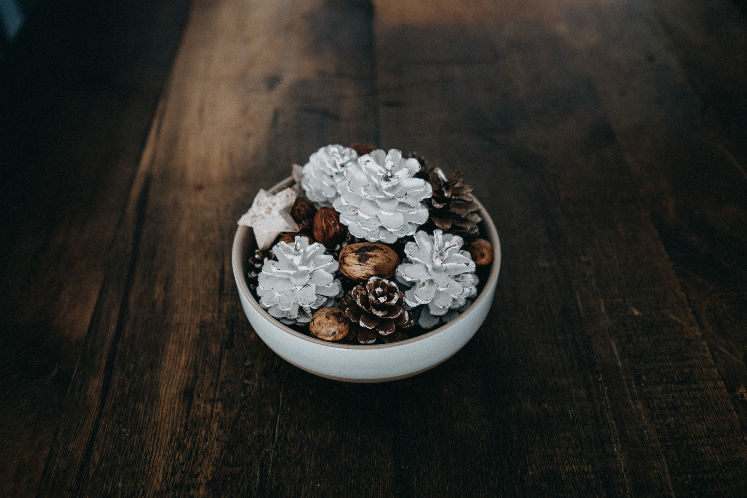 Rustic table with a white bowl filled with pinecones