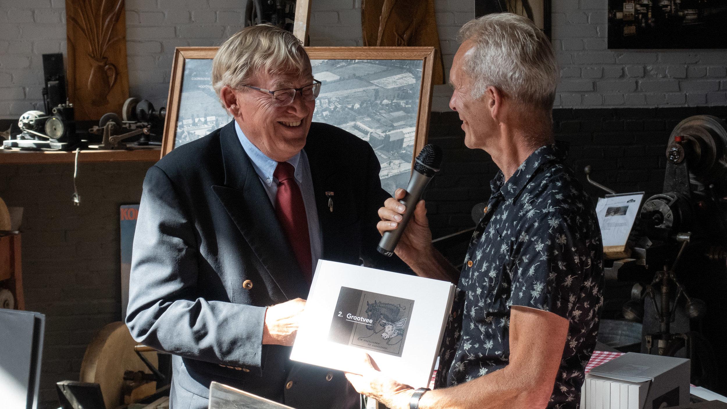 Voorzitter Ben van Dam rijkt het eerste exemplaar van deel 2. Grootvee, uit aan Jan van Riel