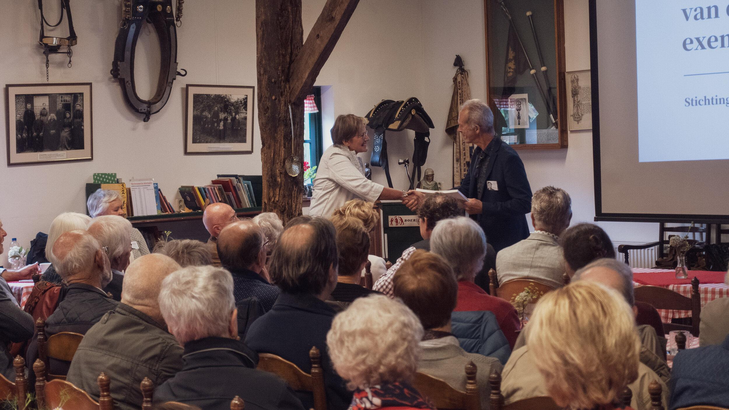 Mevrouw Coby van der Pas, wethouder van Meierijstad ontvangt een eerste exemplaar van deel 4 Landbouwpolitiek uit handen van de voorzitter van de stichting Ben van Dam