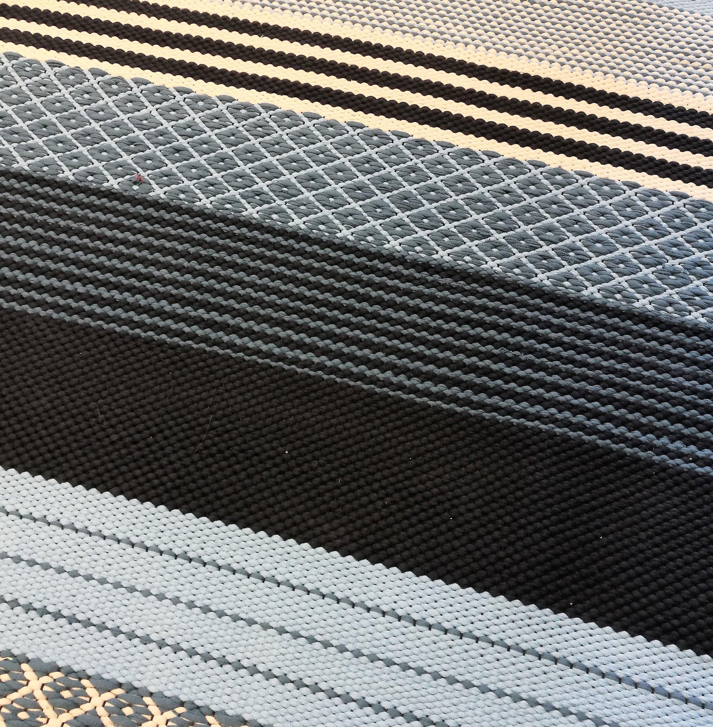 Asiakkaan kutoma raikas matto, jossa on erilaisia palttinalla ja ruusukkaalla kudottuja osioita.