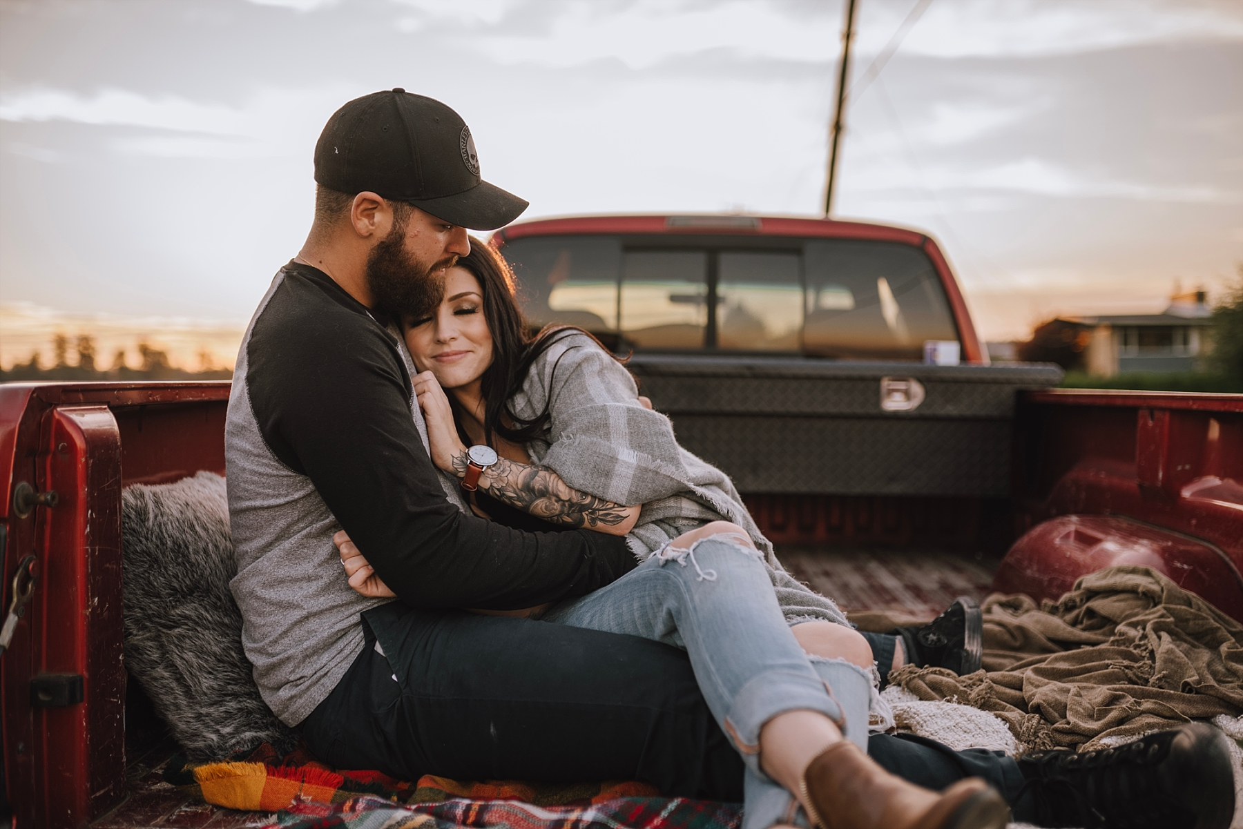 couple cuddling in the back of a truck