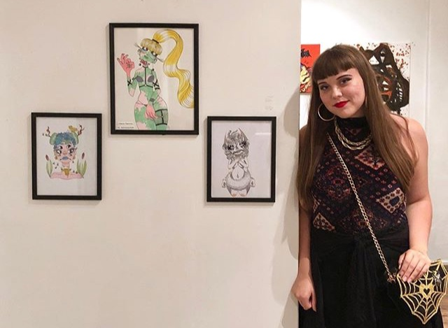 Claire Dennis next to her work, at Color Theory Club II