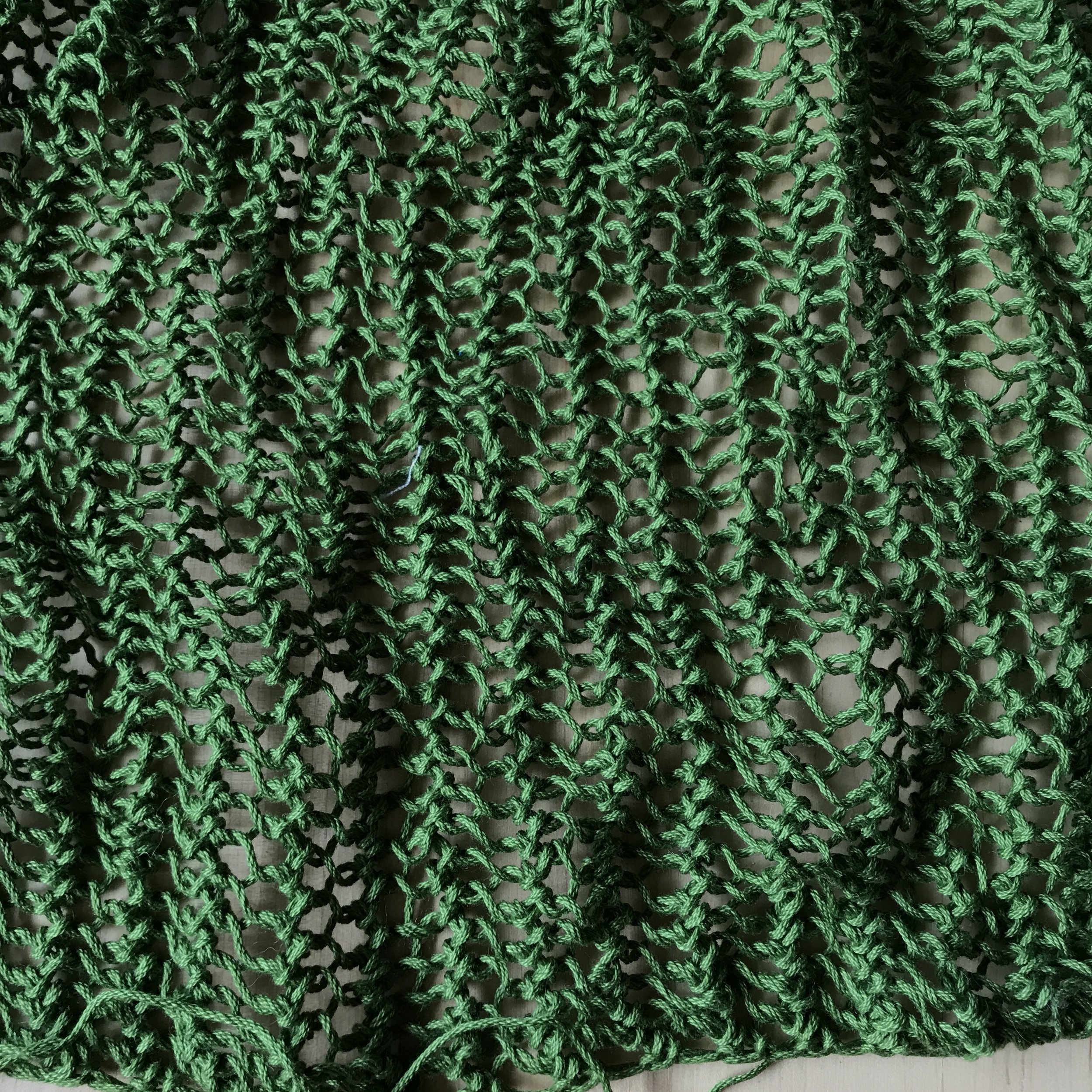 Close up of unblocked fishnet knitted fabric.
