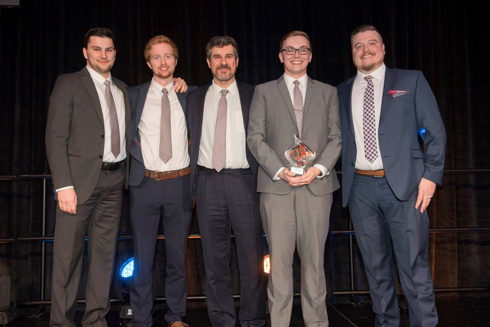 Members of the Canum team (Jayson Brown, Kyle Woods, Felipe Chibante, and Alex Clarkin) accepting the grand prize award from NBIF's Director of Investments, Ray Fitzpatrick.
