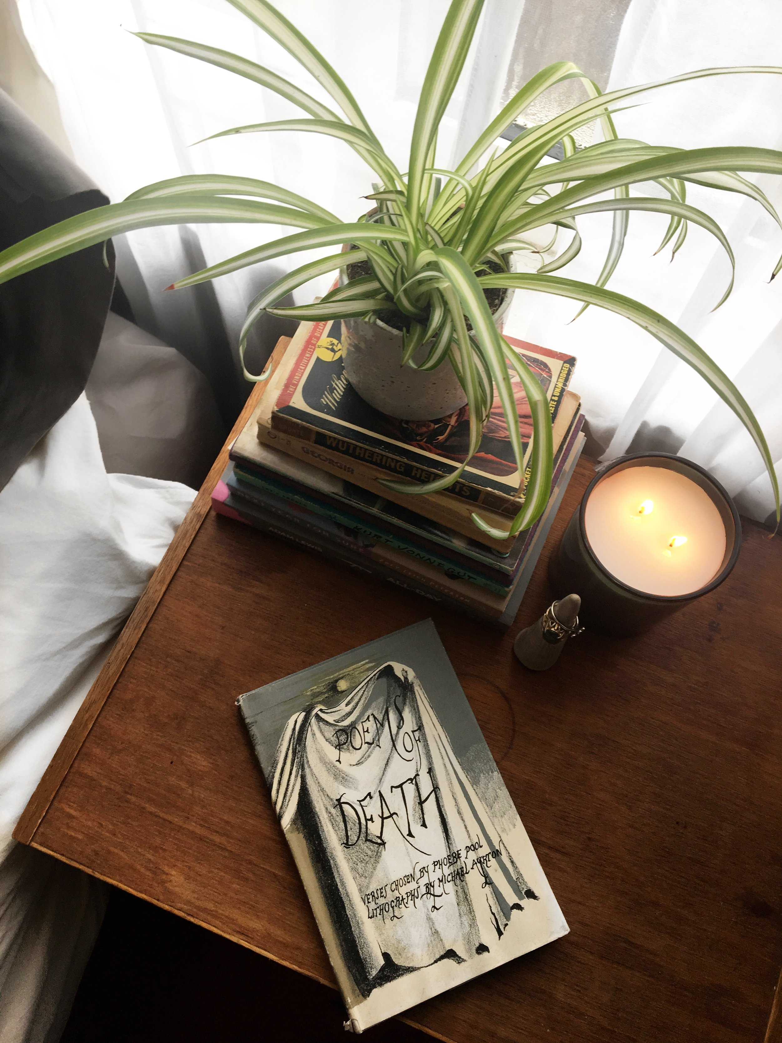 book of death poetry on a bedside table next to a burning candle stack of books spider plant ceramic ring holder lifestyle blogger female blogger feminist blogger Canadian blogger The States of Georgia