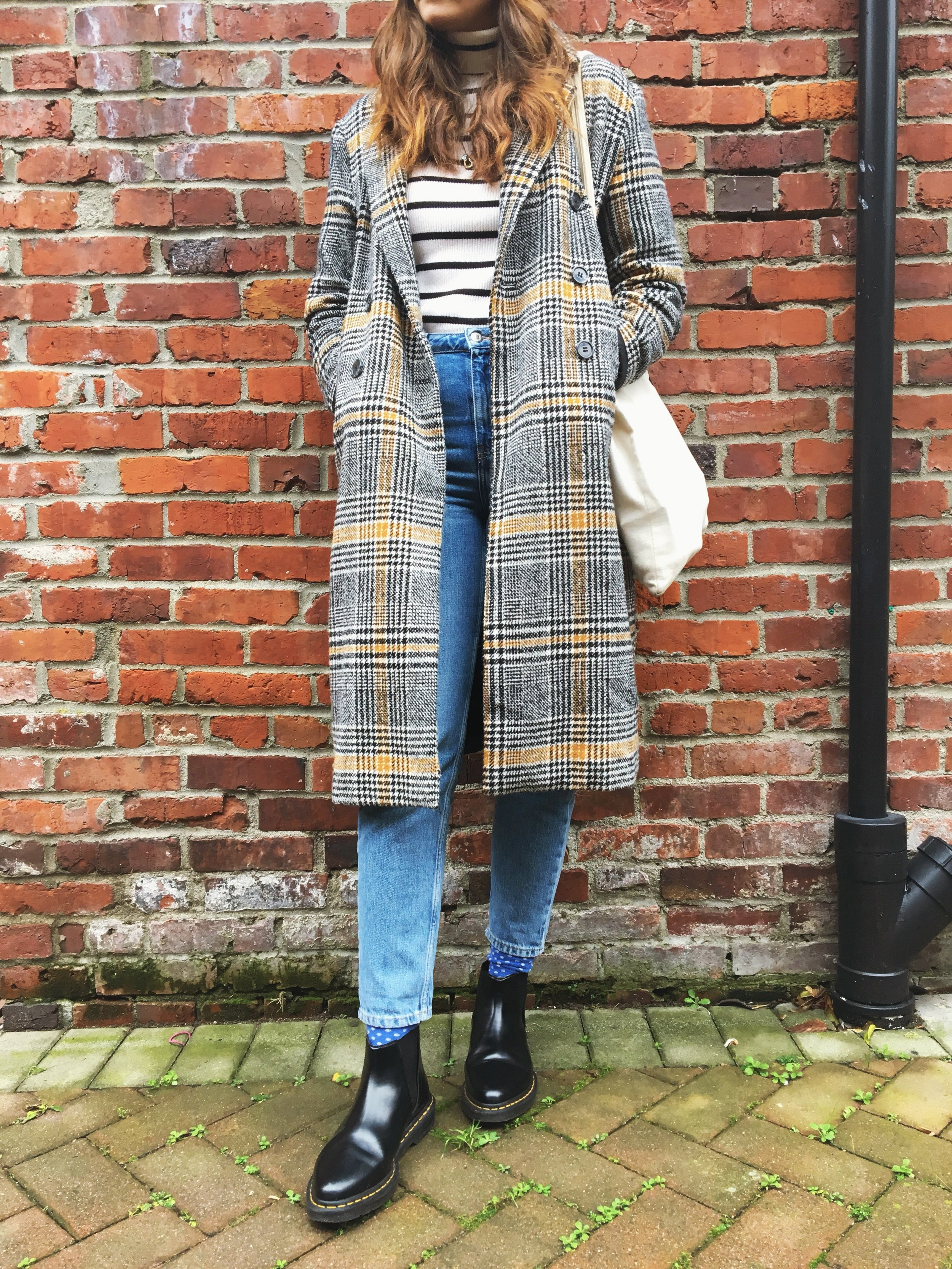 woman standing against a brick wall carrying a white tote wearing striped turtle neck plaid coat jeans and doc martens lifestyle blogger Canadian blogger female feminist blogger